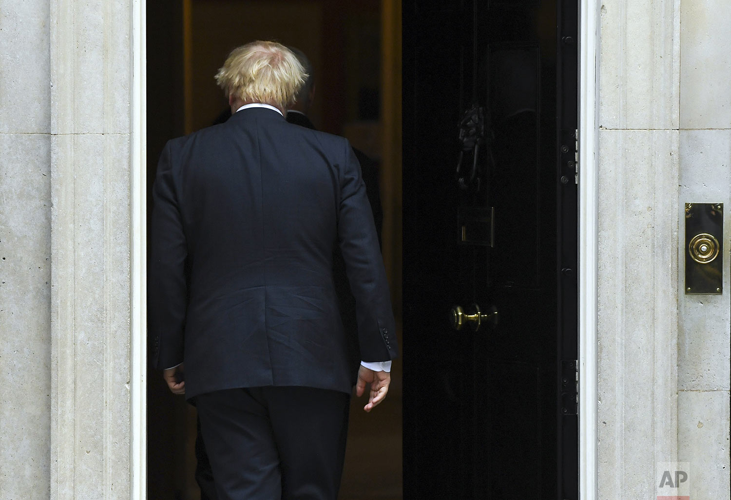 Britain's Prime Minister Boris Johnson walks back into 10 Downing Street after greeting U.S. Vice President Mike Pence  in London, Thursday, Sept. 5, 2019. Boxed in by opponents and abandoned politically even by his own brother, Johnson struggled Thursday to keep his Brexit plans on track. (AP Photo/Alberto Pezzali)