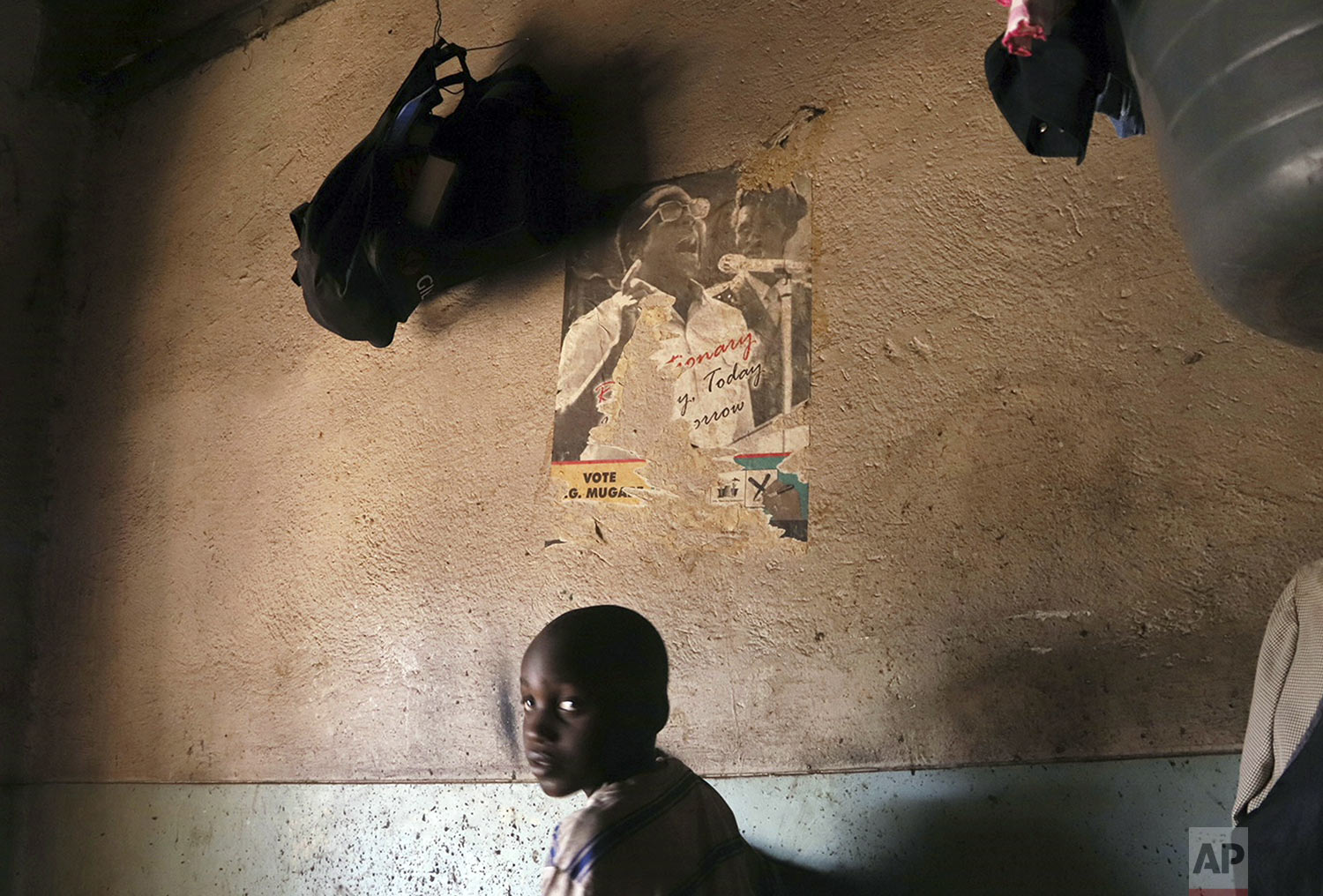A young child passes by an old torn poster of former Zimbabwean President Robert Mugabe in a building in Harare Friday, Sept. 6, 2019. Mugabe, the former leader of Zimbabwe forced to resign in 2017 after a 37-year rule whose early promise was eroded by economic turmoil, disputed elections and human rights violations, has died. He was 95. (AP Photo)