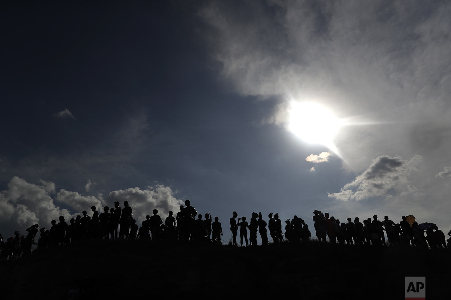 People painted with black grease gather on top of a hill as they take part in the traditional festivities of the Cascamorras festival in Baza, Spain, Friday, Sept. 6, 2019. (AP Photo/Manu Fernandez)