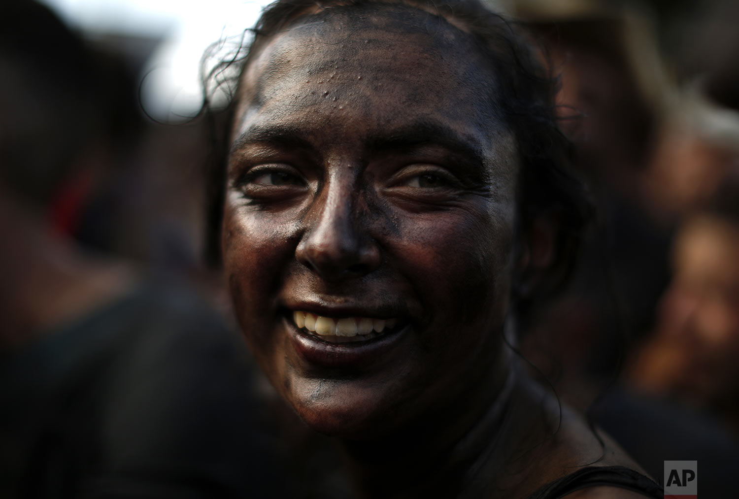 A woman painted with black grease smiles as she takes part at the traditional festivities of the Cascamorras festival in Baza, Spain, Friday, Sept. 6, 2019. (AP Photo/Manu Fernandez)