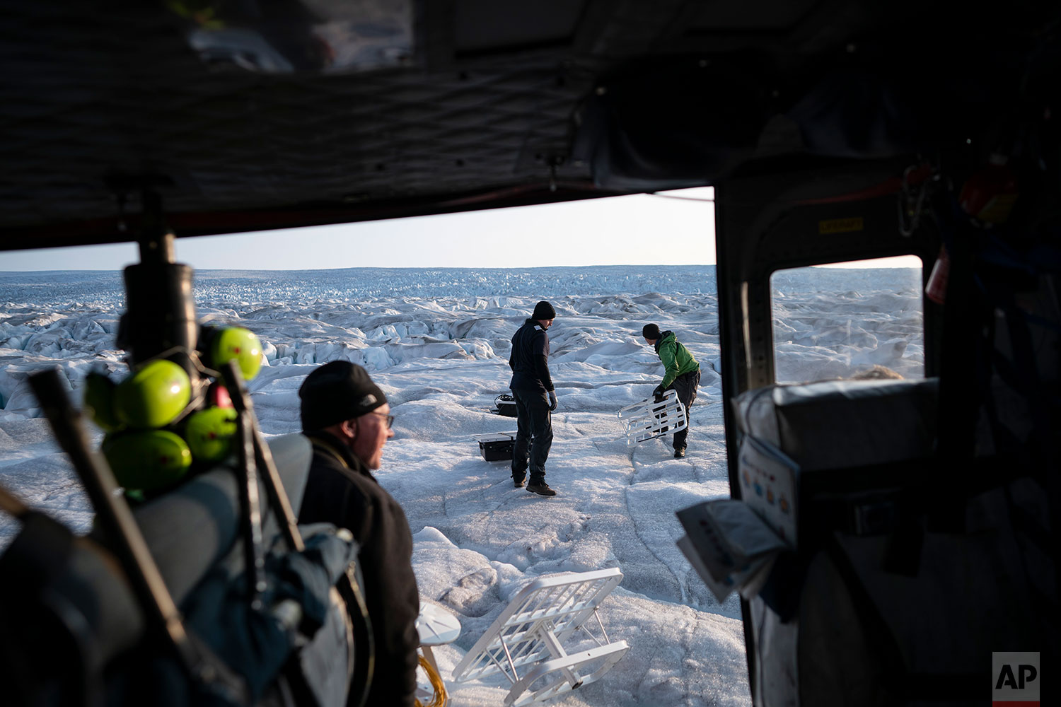 In this Aug. 16, 2019 photo, New York University air and ocean scientist David Holland, left, and field safety officer Brian Rougeux, right, are helped by pilot Martin Norregaard  as they carry antennas out of a helicopter to be installed at the Helheim glacier, in Greenland. (AP Photo/Felipe Dana)