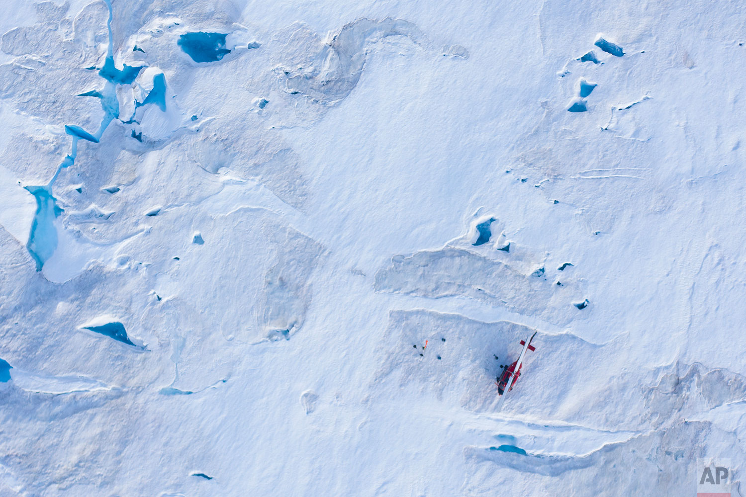 In this Aug. 16, 2019 photo, a helicopter carrying New York University air and ocean scientist David Holland and his team sits on the ice as they install a radar and GPS at the Helheim glacier, in Greenland. (AP Photo/Felipe Dana)