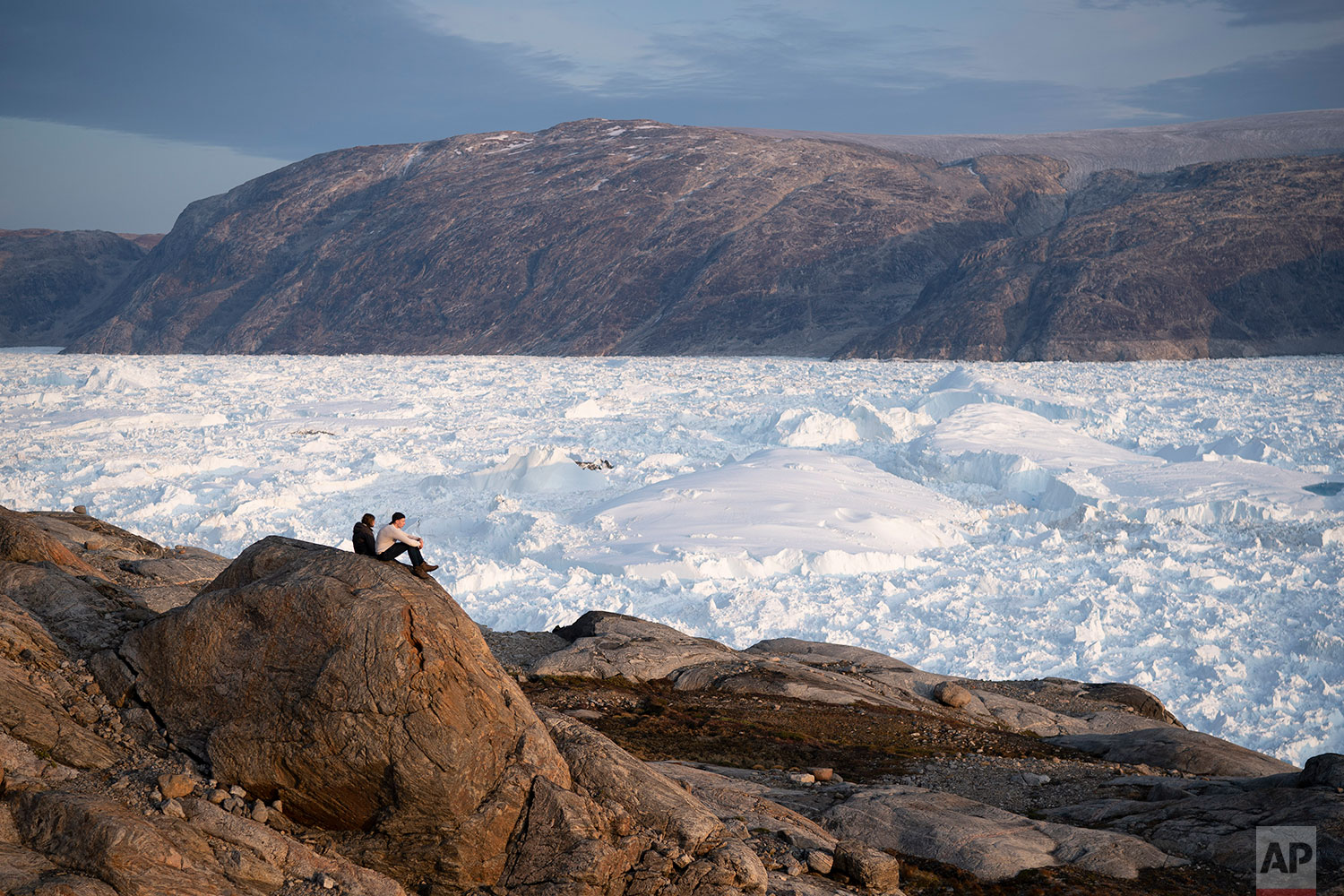 In this Aug. 16, 2019 photo, NYU student researchers sit on top of a rock overlooking the Helheim glacier in Greenland. (AP Photo/Felipe Dana)