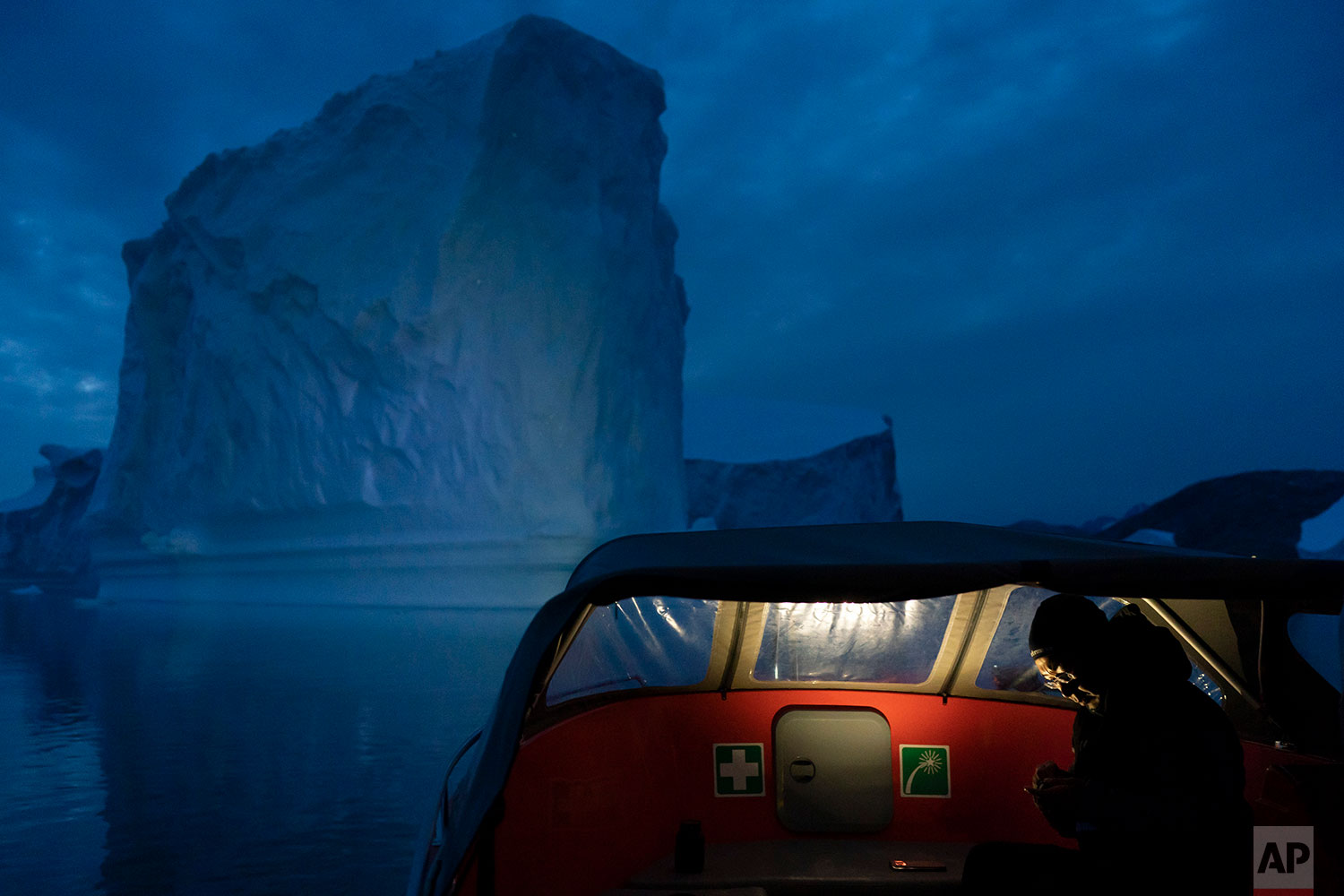 In this Aug. 15, 2019 photo, a boat navigates at night next to a large iceberg in eastern Greenland. (AP Photo/Felipe Dana)
