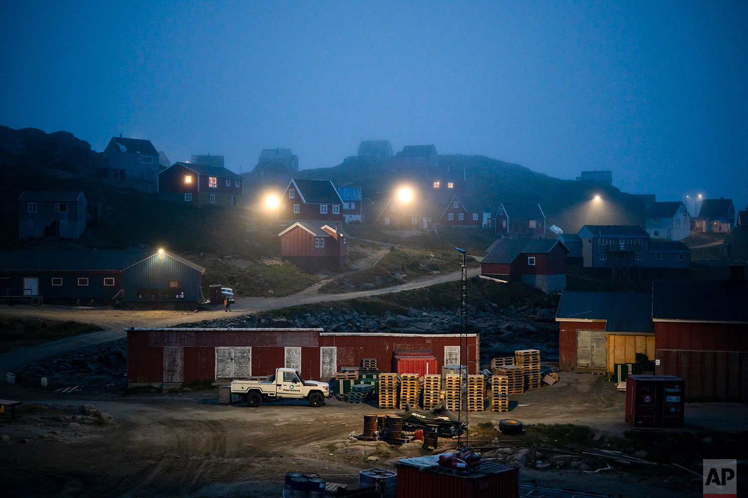 In this Aug. 15, 2019 photo, homes are partly covered by early morning fog in Kulusuk, Greenland. (AP Photo/Felipe Dana)