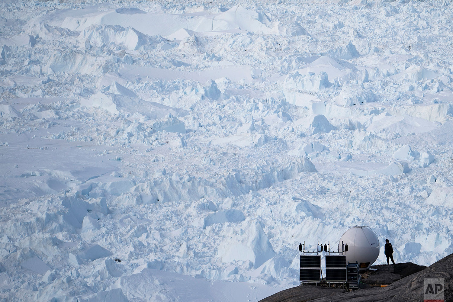 In this Aug. 16, 2019 photo, a woman stands next to an antenna at a NYU base camp at the Helheim glacier in Greenland. (AP Photo/Felipe Dana)