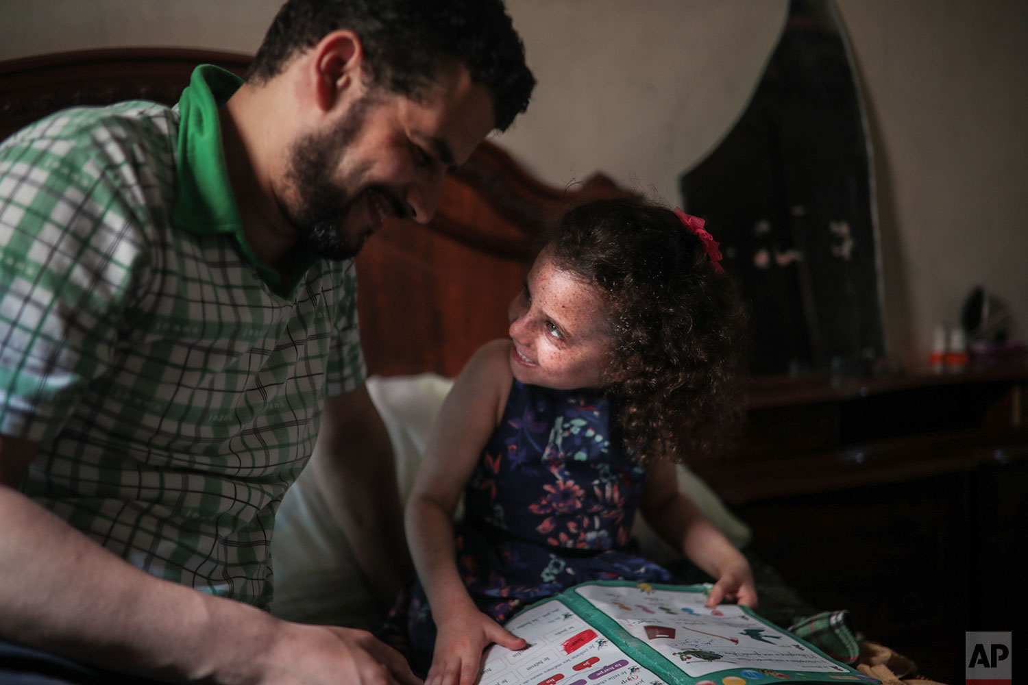 In this Tuesday, July 23, 2019 photo, Said El Mohamadi shares a moment with his 6 year old daughter Romaisae who is affected by a rare disorder called xeroderma pigmentosum, or XP, in their home in the town of Sale, near Rabat, Morocco. (AP Photo/Mosa'ab Elshamy)