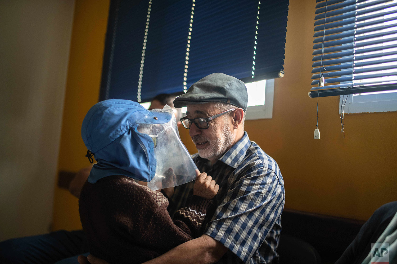 In this Wednesday, July 24, 2019 photo, Habib El Ghazaoui, a father who runs the Association for Solidarity with Children of the Moon, plays with 8 year old Mustapha who is affected by a rare genetic disorder called xeroderma pigmentosum, or XP, inside a hospital in Casablanca, Morocco. (AP Photo/Mosa'ab Elshamy)