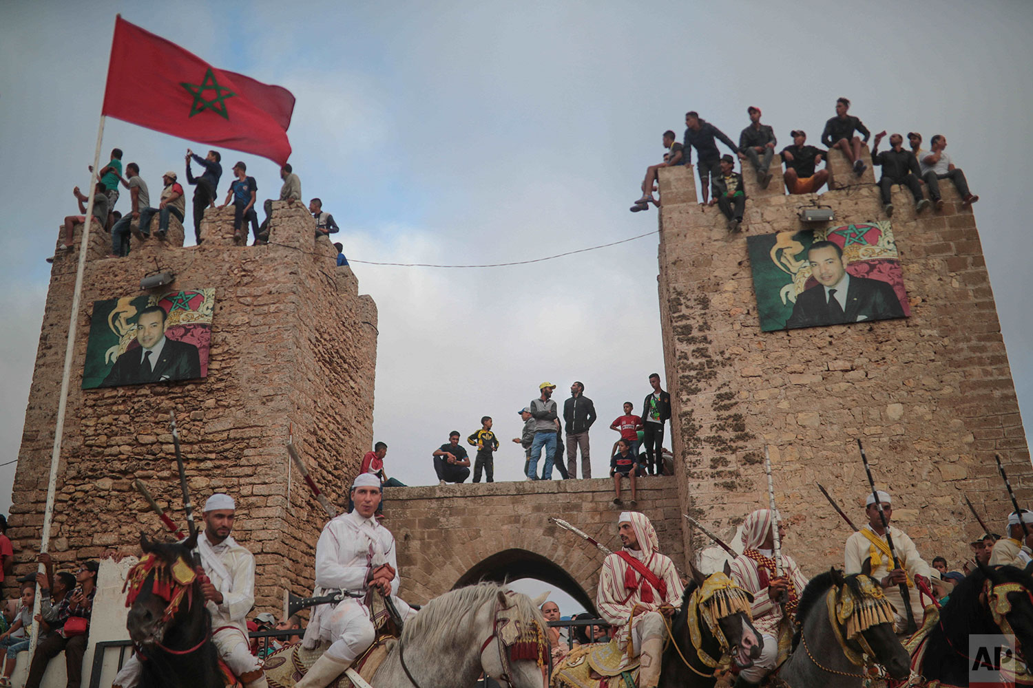 In this Thursday, July 25, 2019 photo, people watch atop an ancient wall as riders wait during Tabourida, a traditional horse riding show also known as Fantasia, in the coastal town of El Jadida, Morocco.  (AP Photo/Mosa'ab Elshamy)