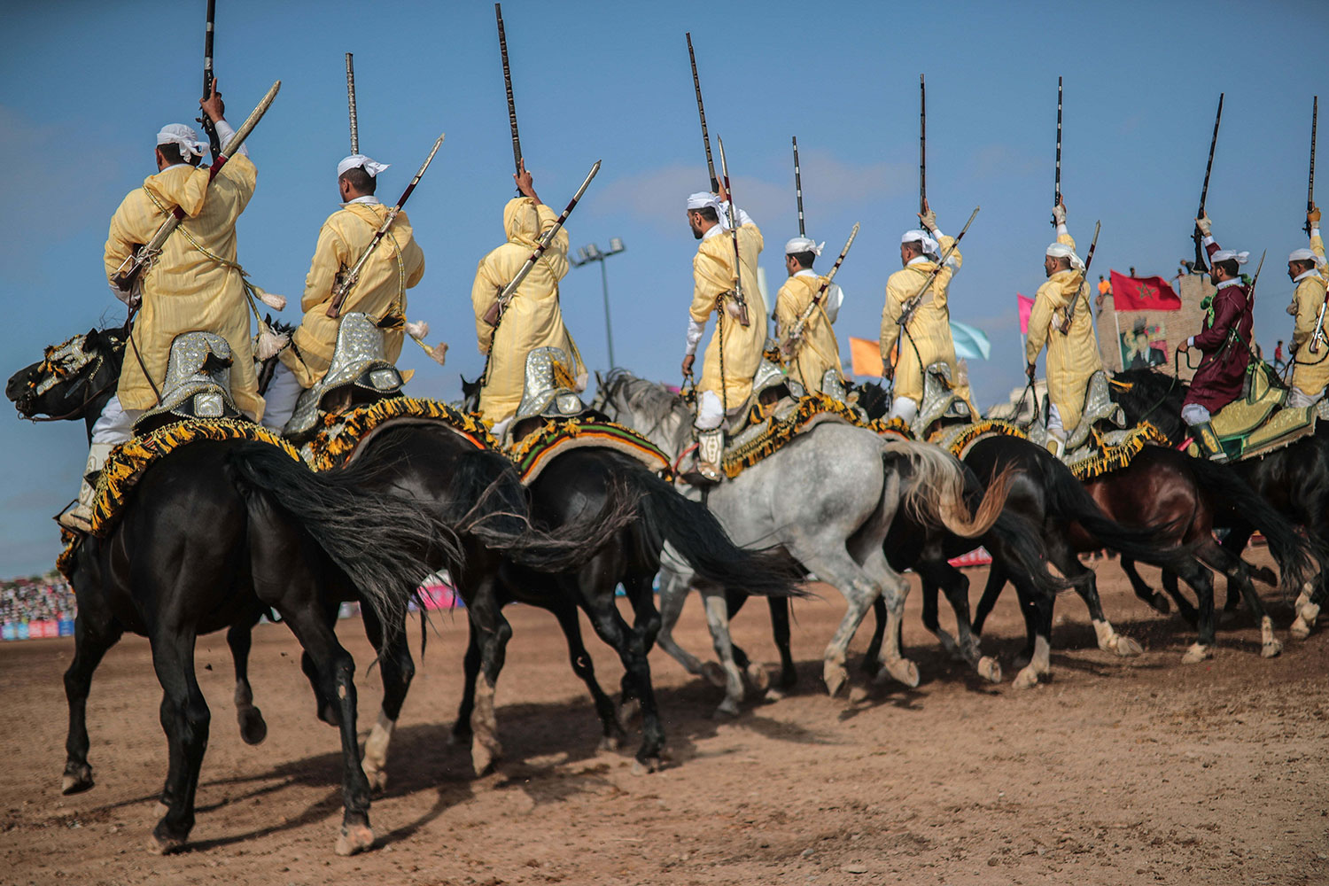 In this Thursday, July 25, 2019 photo, a troupe charges and hold their rifles before firing, during Tabourida, a traditional horse riding show also known as Fantasia, in the coastal town of El Jadida, Morocco. (AP Photo/Mosa'ab Elshamy)