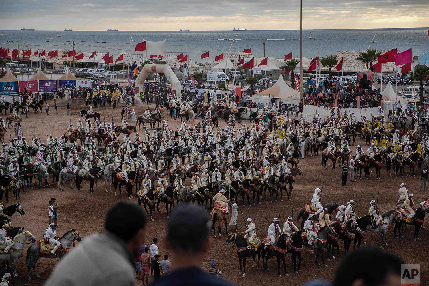 In this Thursday, July 25, 2019 photo, people watch as horse riders wait for their turn to take part in an equestrian show known as Fantasia or Tabourida, in the coastal town of El Jadida, Morocco. (AP Photo/Mosa'ab Elshamy)