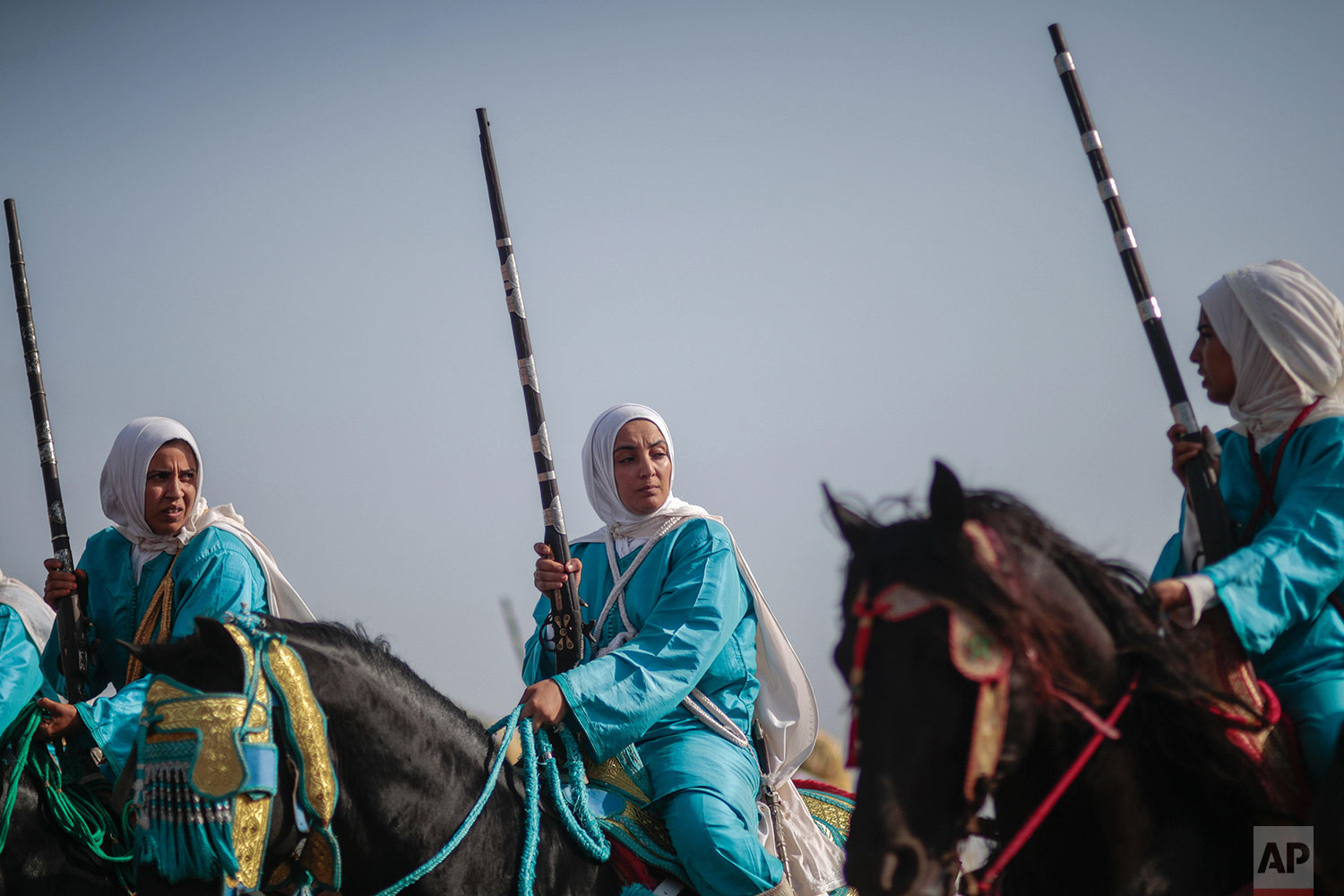 In this Thursday, July 25, 2019 photo, a female troupe prepares to take part in Tabourida, a traditional horse riding show also known as Fantasia, in the coastal town of El Jadida, Morocco.  (AP Photo/Mosa'ab Elshamy)