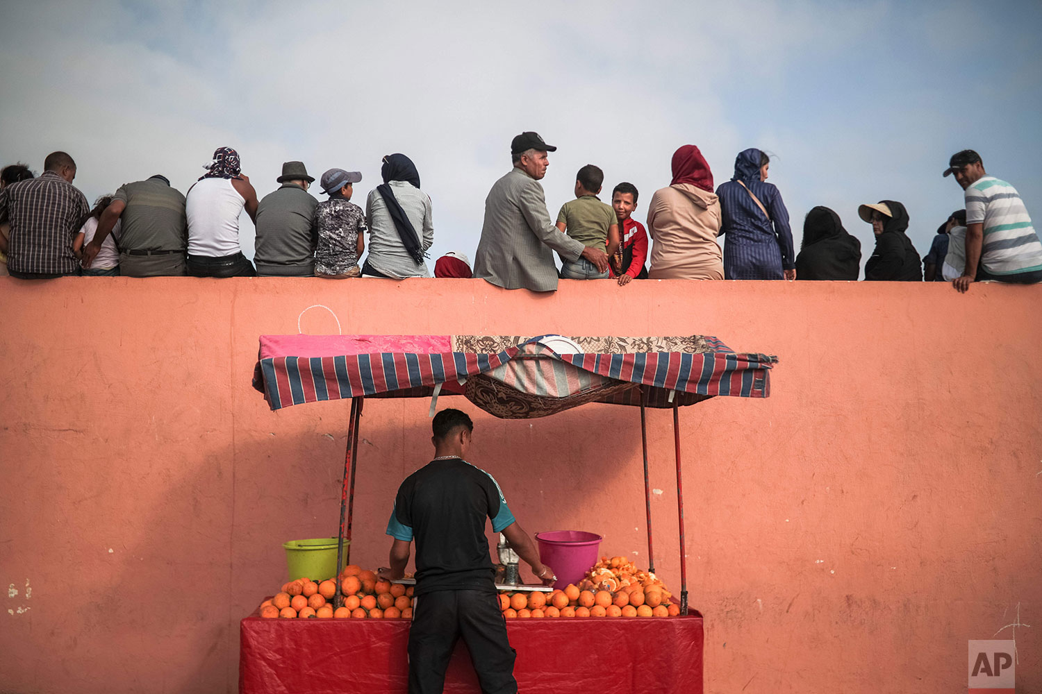 In this Thursday, July 25, 2019 photo, a vendor sells orange juice as people sit on a fence to watch a horsemanship show known as Fantasia or Tabourida, in the coastal town of El Jadida, Morocco. (AP Photo/Mosa'ab Elshamy)