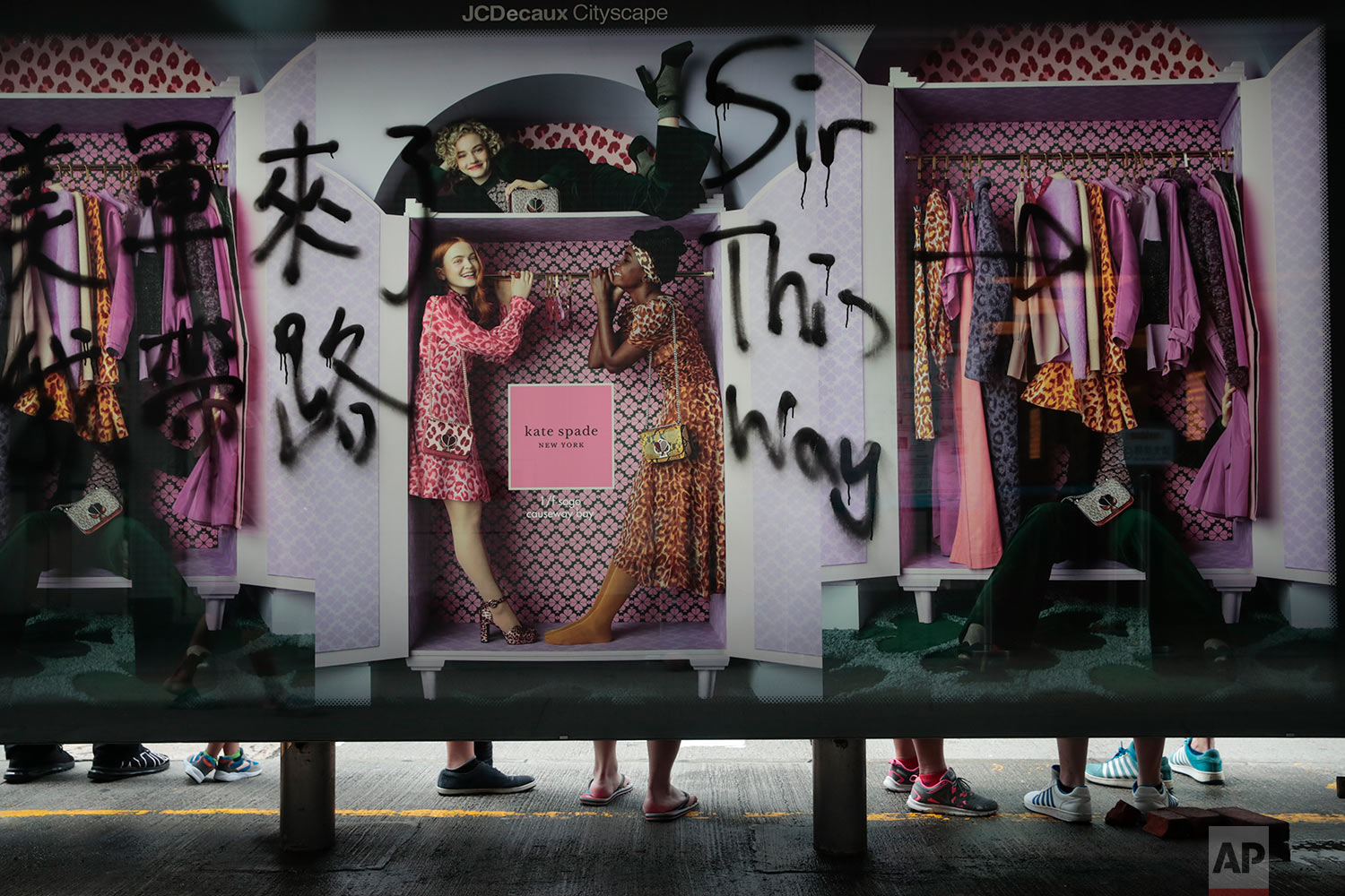 People wait for buses at a bus stop vandalized by protesters in Hong Kong, Sept. 1, 2019. (AP Photo/Jae C. Hong)