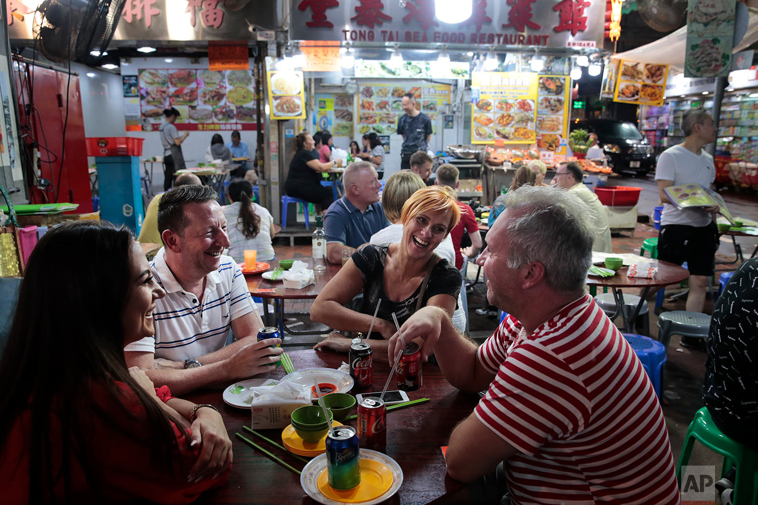 A group of British tourists share a laugh around a dinner table at Temple Street Night Market in Hong Kong, Sept. 2, 2019. (AP Photo/Jae C. Hong)