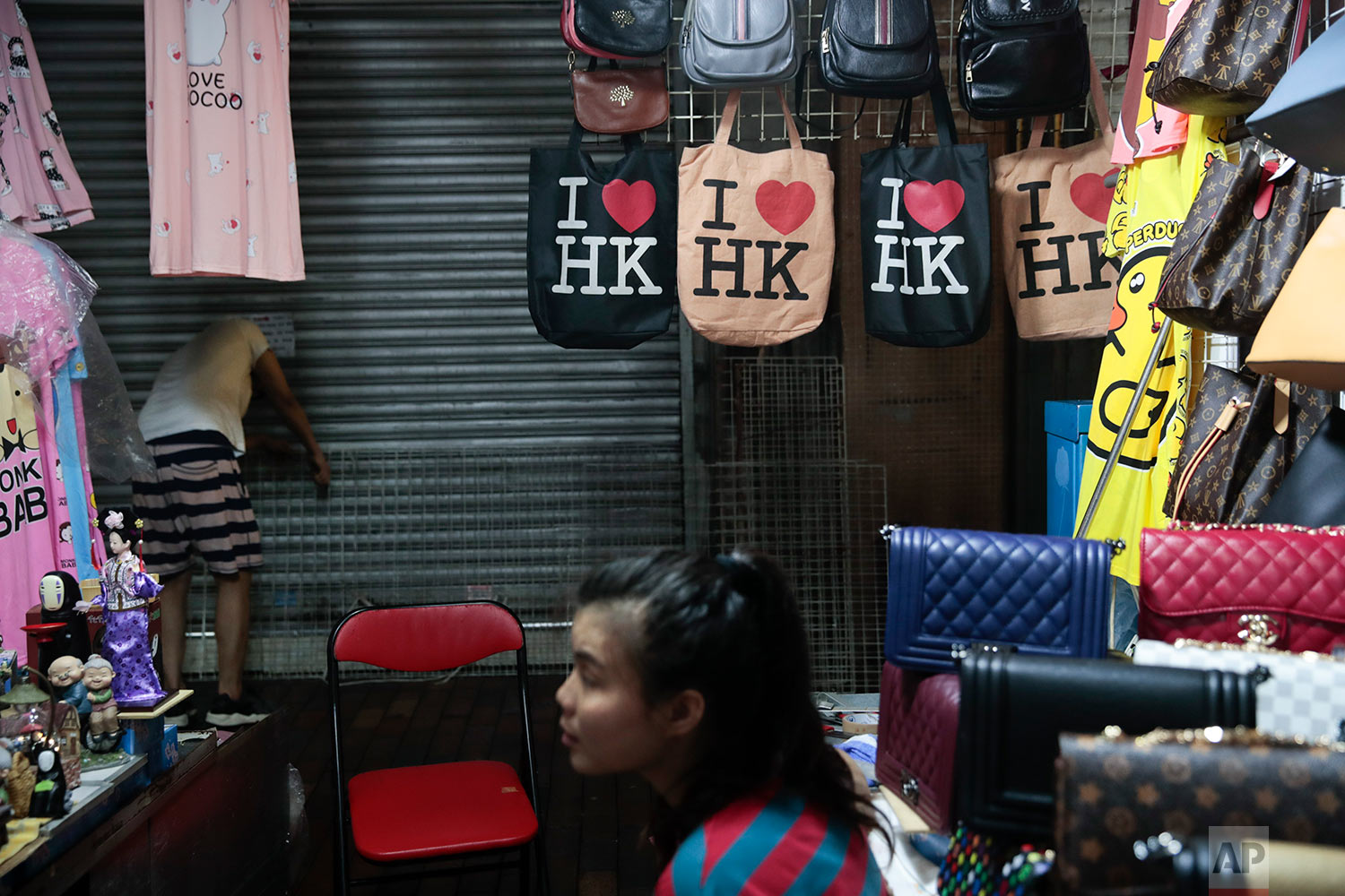 "A vendor selling handbags along with a few ""I heart HK"" tote bags, sits in her booth at Temple Street Night Market in Hong Kong, Sept. 2, 2019. (AP Photo/Jae C. Hong)"