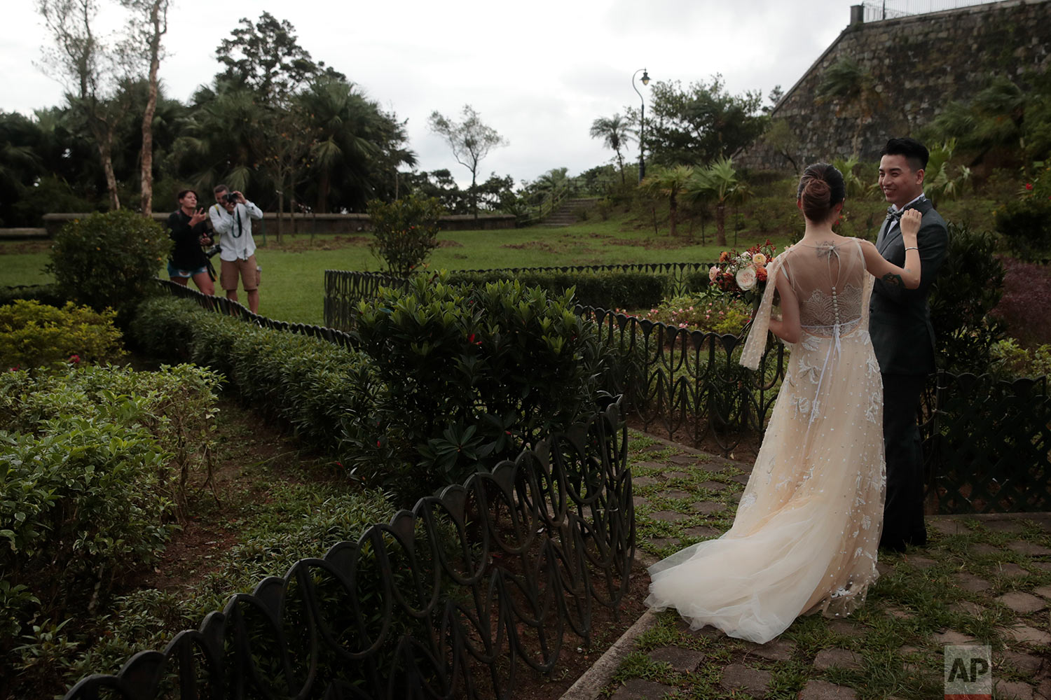 A bride fixes her groom's bow tie during a wedding photoshoot on the top of the Victoria Peak in Hong Kong, Sept. 1, 2019. (AP Photo/Jae C. Hong)