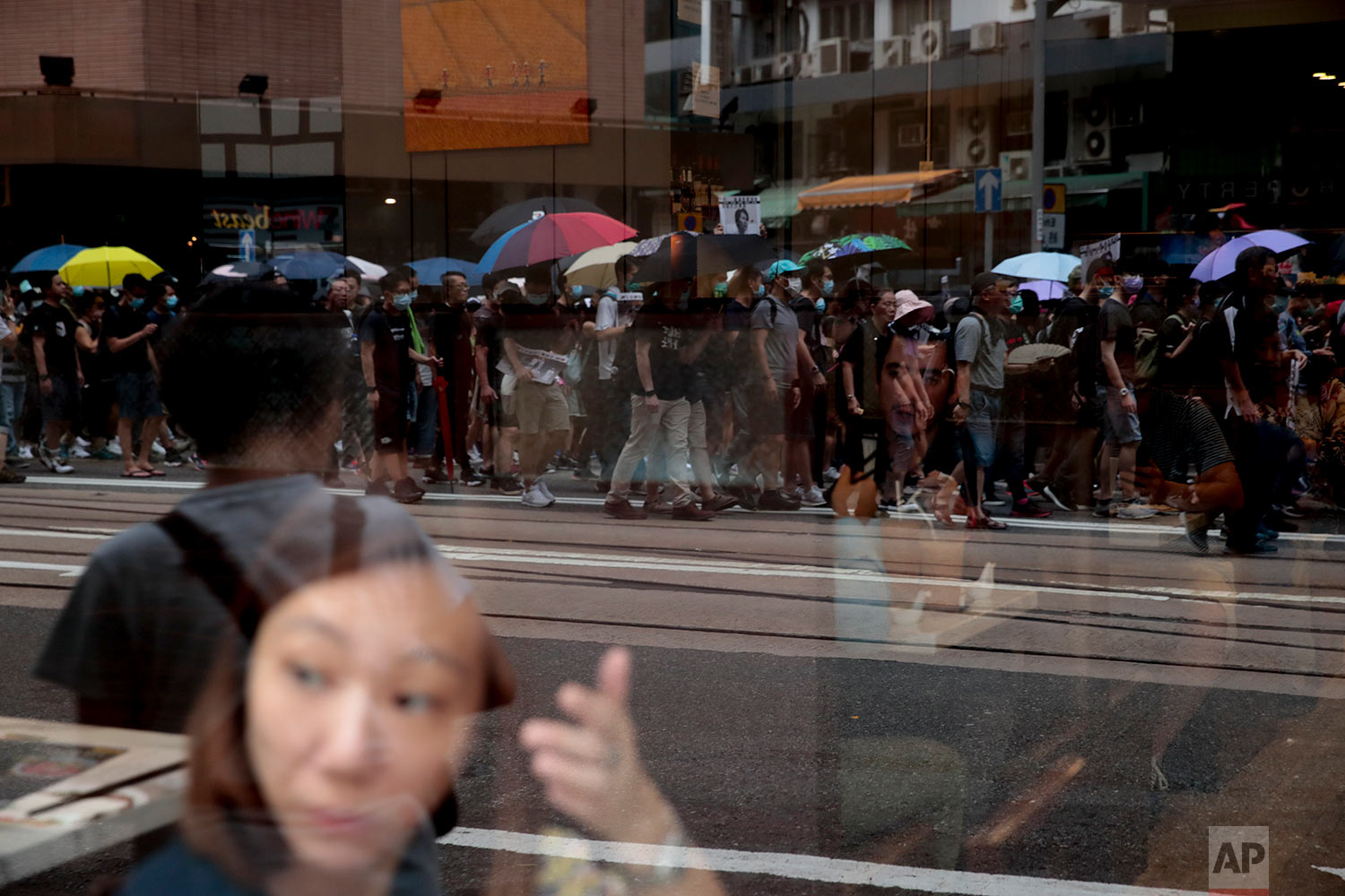 Protesters are reflected on a window as they march during a pro-democracy protest in Wan Chai, Hong Kong, Aug. 31, 2019. (AP Photo/Jae C. Hong)