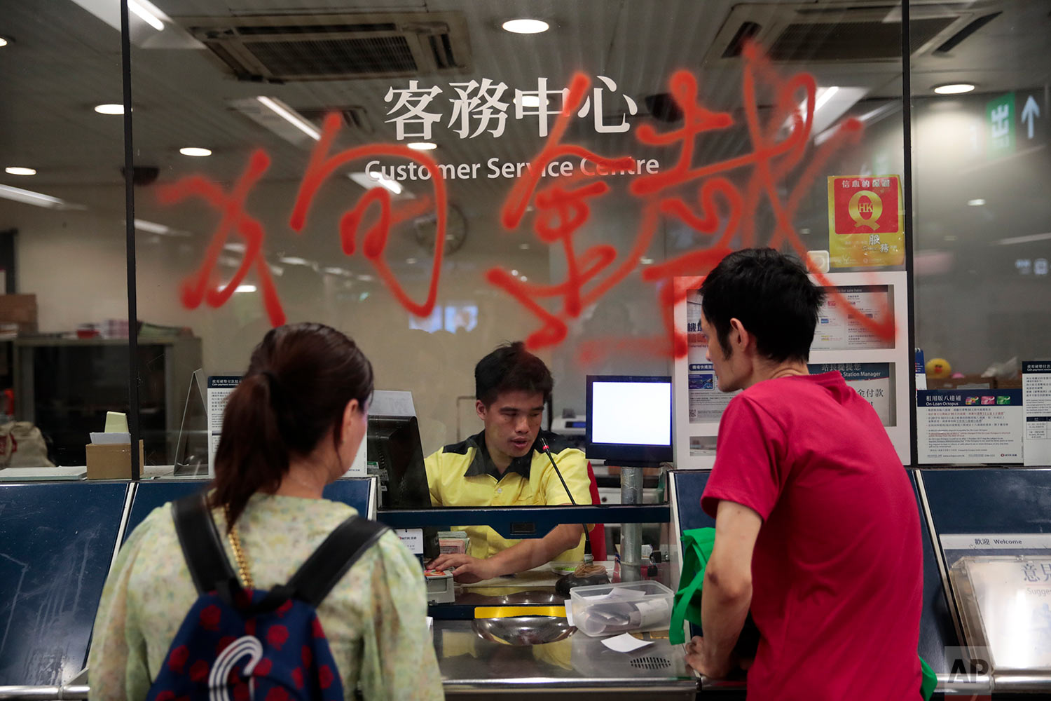 People purchase subway tickets from a vandalized customer center in Hong Kong, Aug. 31, 2019. (AP Photo/Jae C. Hong)