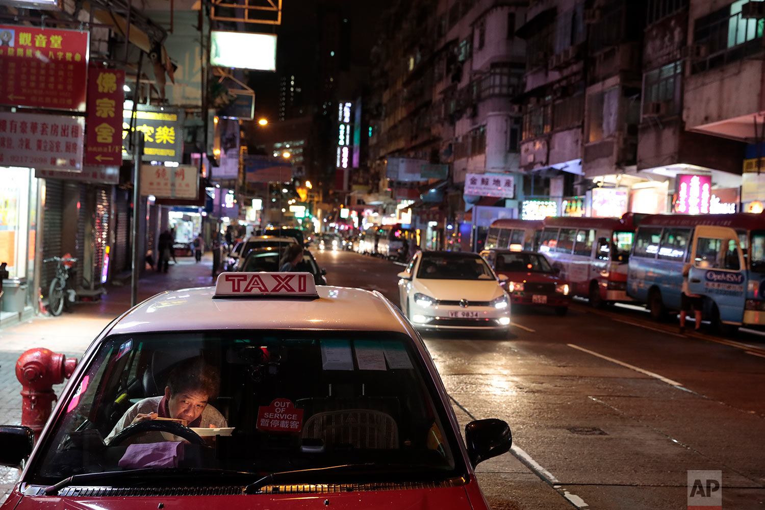 A taxi driver eats his late dinner in his car near the Temple Street Night Market in Hong Kong, Sept. 2, 2019. (AP Photo/Jae C. Hong)