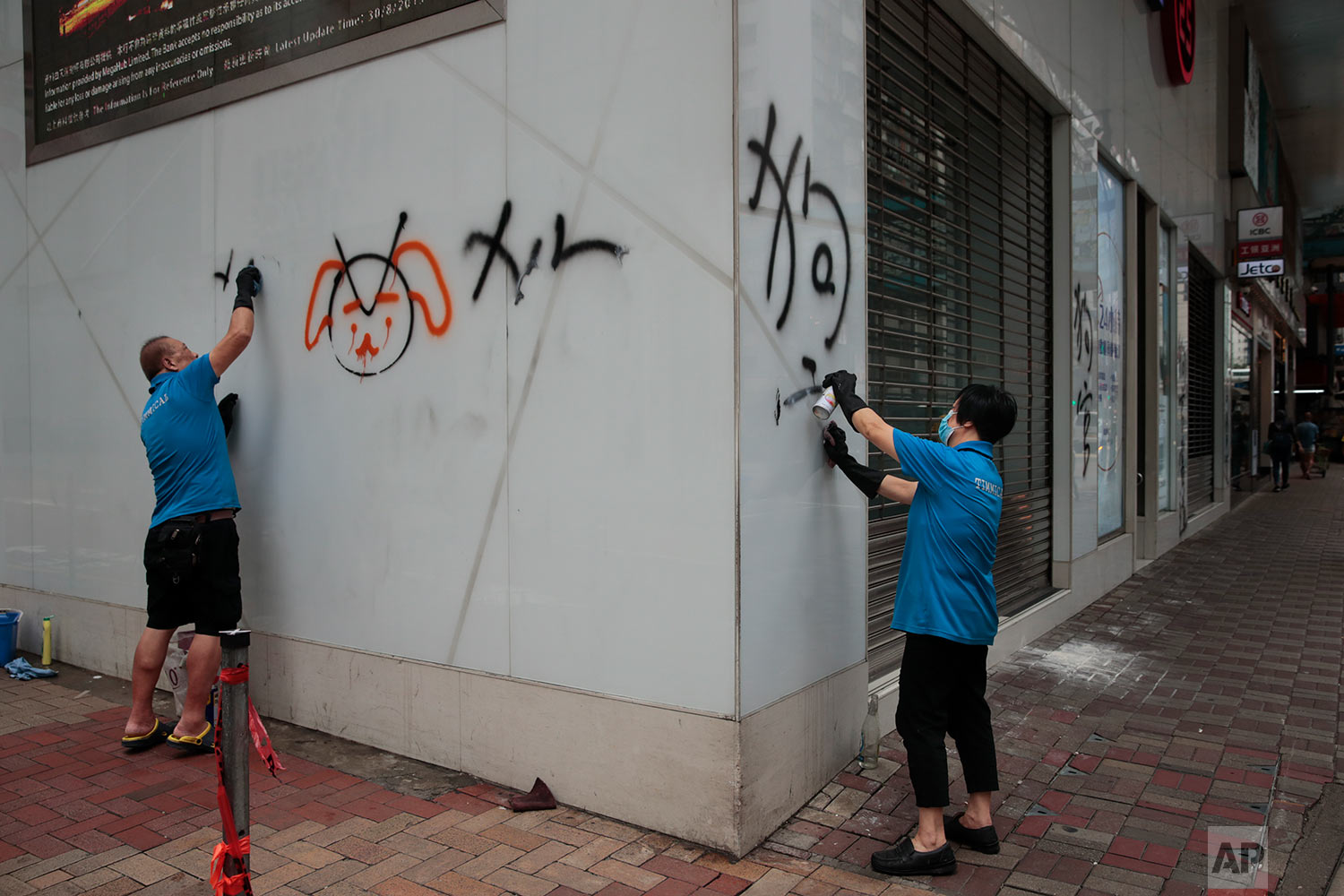 Workers remove graffiti left by protesters during a protest the night before in Hong Kong, Sept. 1, 2019. (AP Photo/Jae C. Hong)