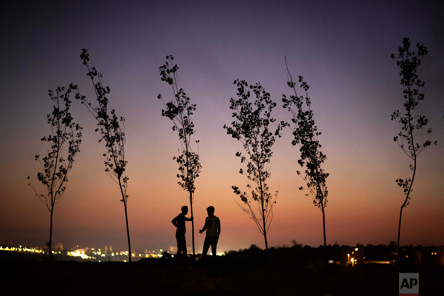 Boys stand atop a hill where a bonfire is lit in celebration of Ashura, in Sale, near Rabat, Morocco, Sept. 9, 2019. (AP Photo/Mosa'ab Elshamy)