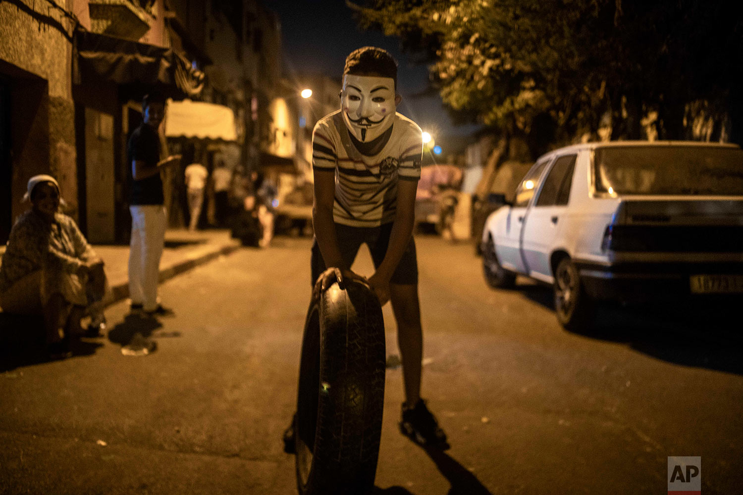 A boy wearing a vendetta mask drags a tire to be lit in a bonfire as part of Ashura celebrations, in Sale, near Rabat, Morocco, Sept. 9, 2019. (AP Photo/Mosa'ab Elshamy)