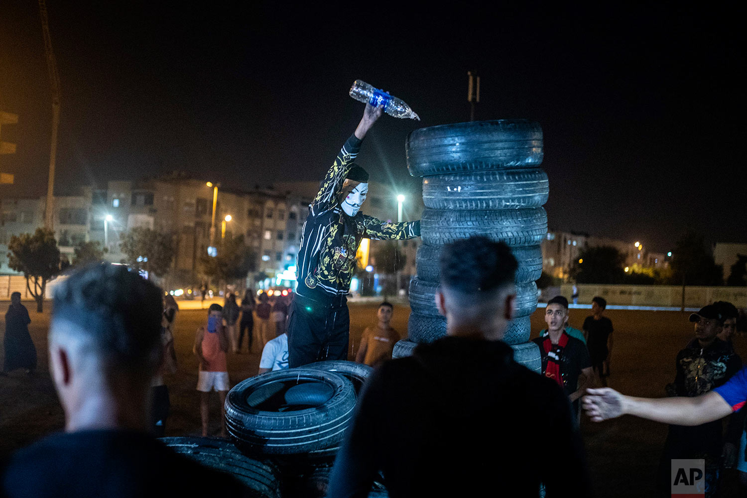 A youth pours kerosene over tires to light a bonfire in celebration of Ashura, in Sale, near Rabat, Morocco, Sept. 9, 2019. (AP Photo/Mosa'ab Elshamy)