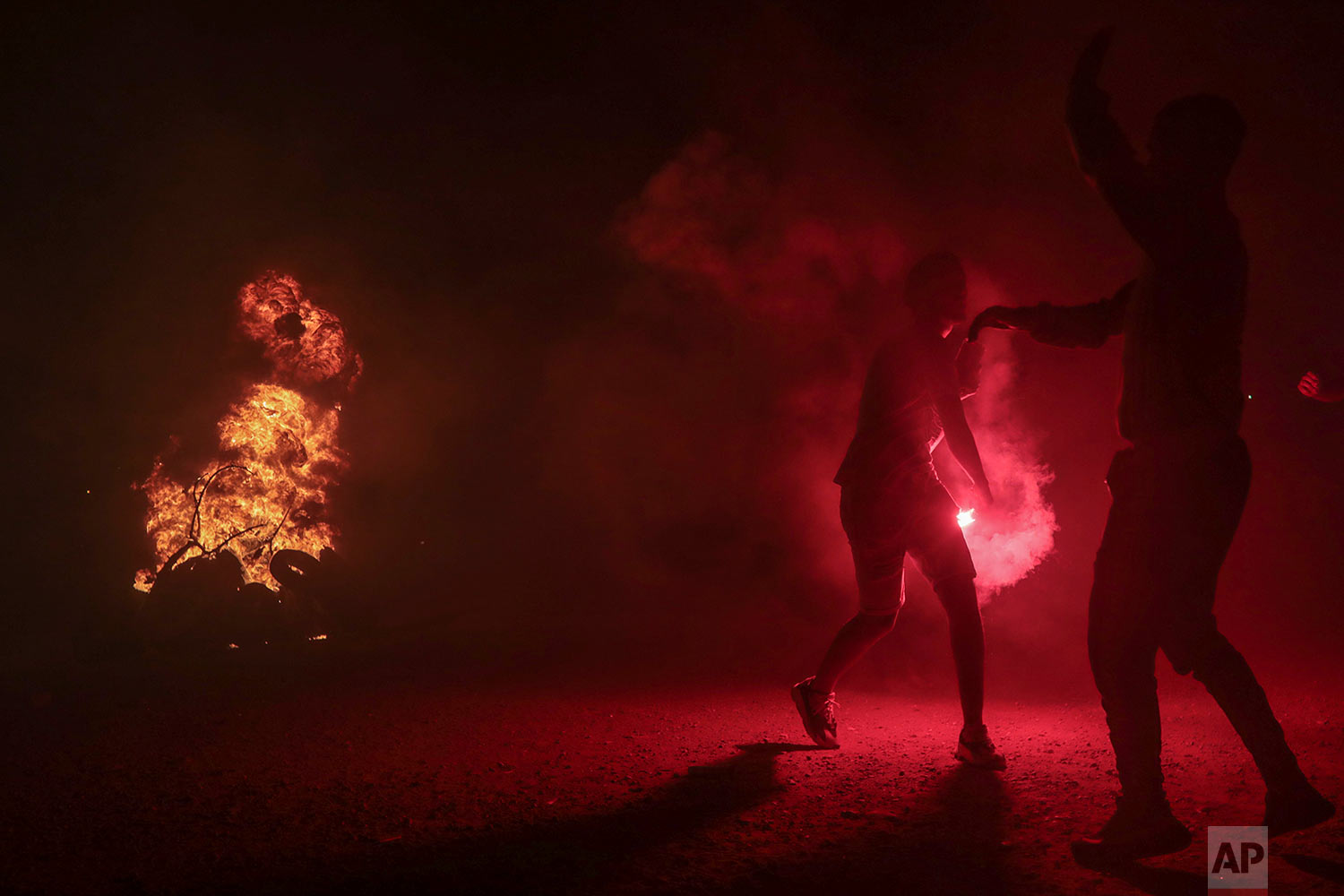 Youths, mostly football ultras, light flares in celebration of Ashura, in Sale, near Rabat, Morocco, Sept. 9, 2019. (AP Photo/Mosa'ab Elshamy)