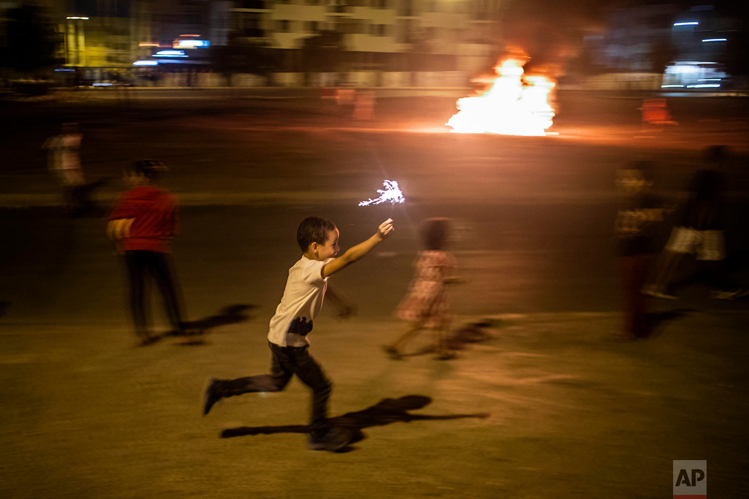 A child runs with a sparkler as a bonfire is lit in the distance in celebration of Ashura, in Sale, near Rabat, Morocco, Sept. 9, 2019. (AP Photo/Mosa'ab Elshamy)