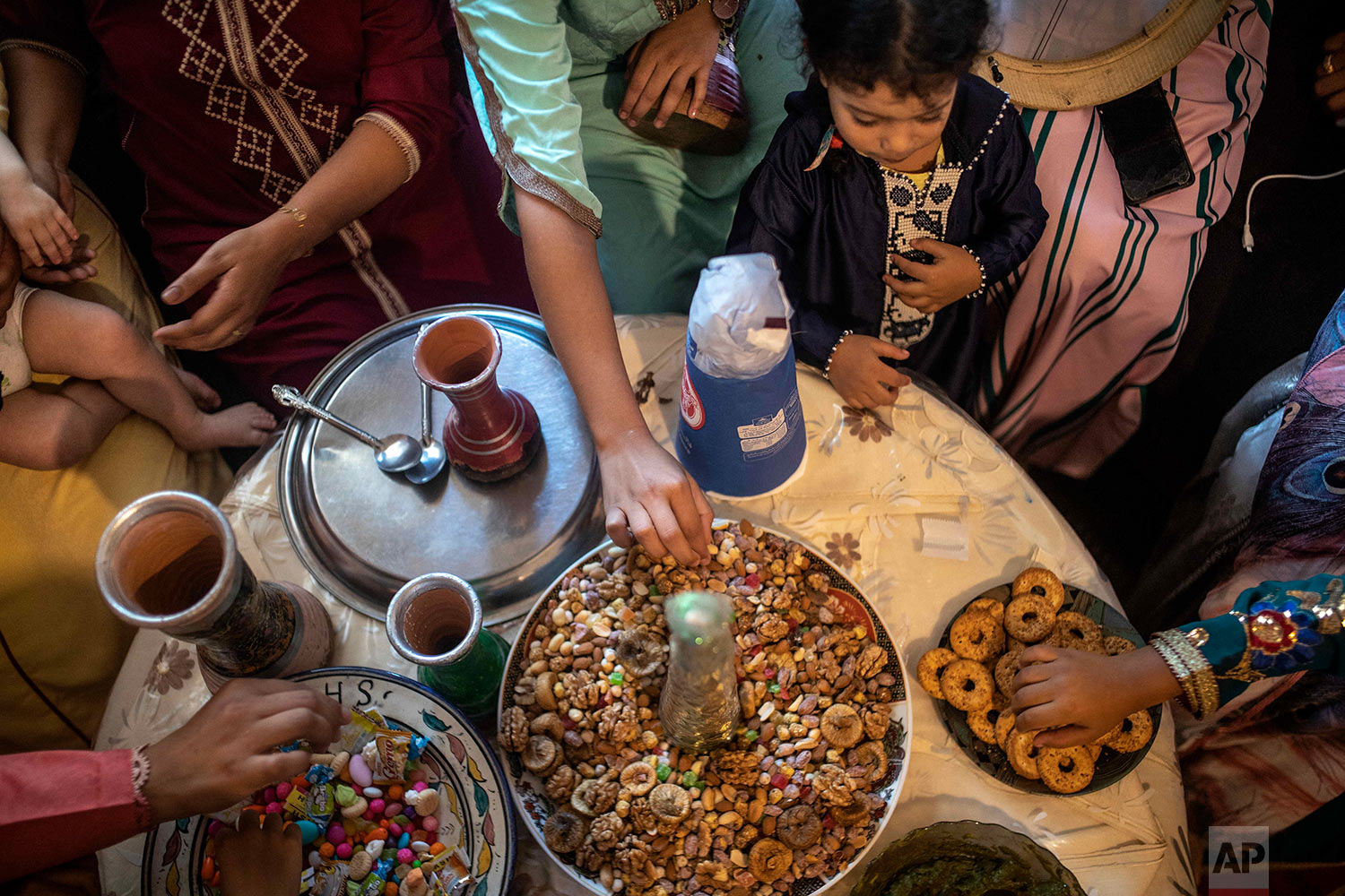 Woman and children eat dried fruits and treats at a home to celebrate the occasion of Ashura, in Sale, near Rabat, Morocco, Sept. 10, 2019. (AP Photo/Mosa'ab Elshamy)