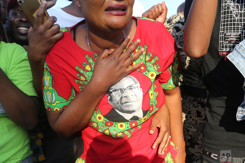Supporters of Zimbabwe's former ruler Robert Mugabe react upon the arrival of his remains at RG Mugabe airport in Harare, Sept, 11, 2019. (AP Photo/Tsvangirayi Mukwazhi)