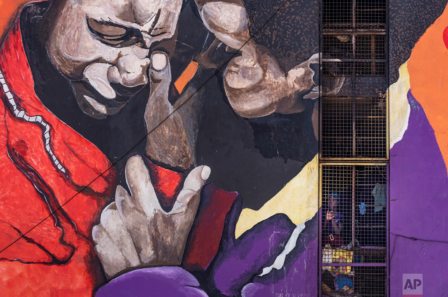 A resident looks out from the stairwell of her housing block, on which is painted an informational mural against sexual abuse, in the low income neighborhood of Mbare, known to have many supporters of former president Robert Mugabe's ZANU-PF party, in the capital Harare, Zimbabwe, Sept. 9, 2019. (AP Photo/Ben Curtis)