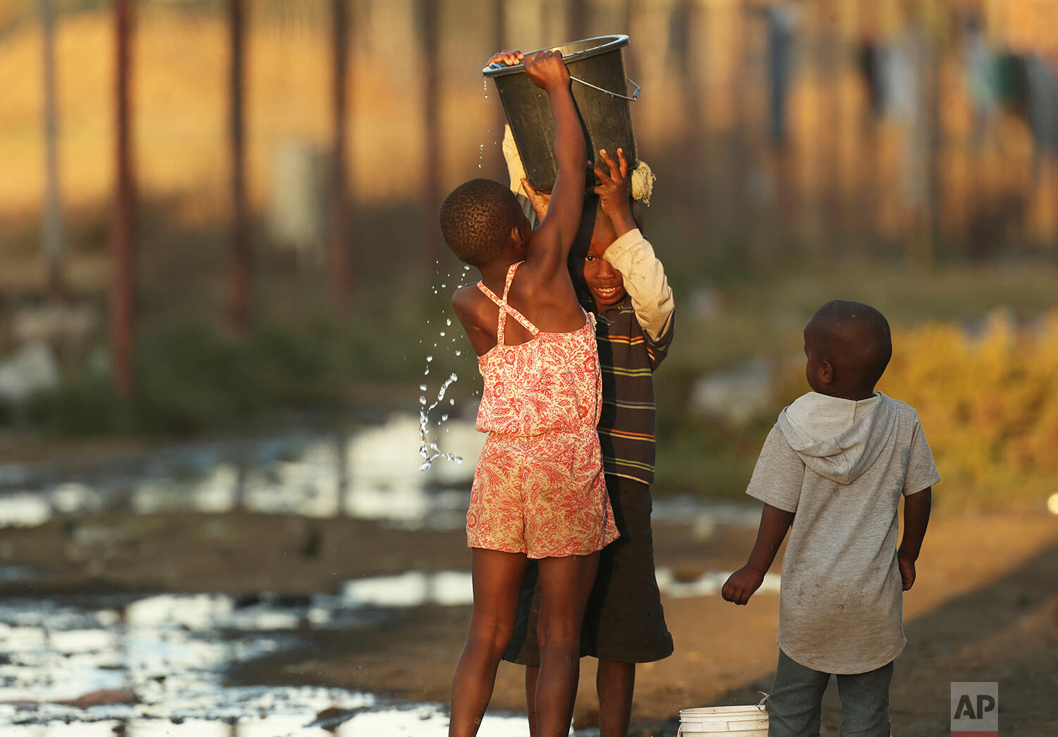 Children help each other to carry a bucket filled with water in Harare, Sept. 8, 2019. (AP Photo/Tsvangirayi Mukwazhi)