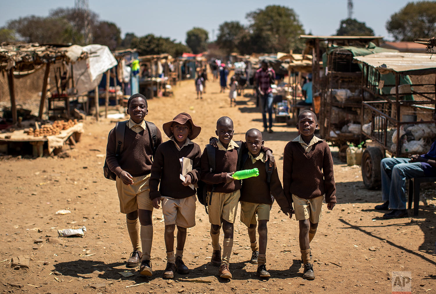 Schoolboys walk back home on the first day of the school term, in Kuwadzana, on the outskirts of the capital Harare, in Zimbabwe, Sept. 10, 2019. (AP Photo/Ben Curtis)