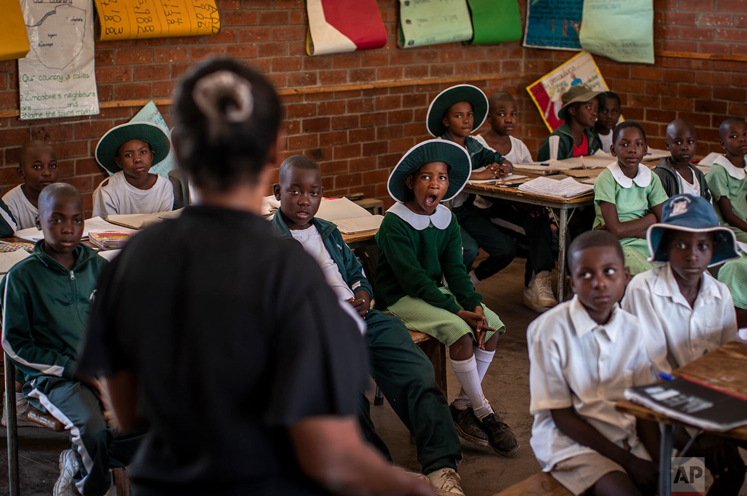 Schoolchildren attend a class in the Shona language on the first day of term at the Vimbai Primary School in Norton, west of the capital Harare, in Zimbabwe, Sept. 10, 2019. (AP Photo/Ben Curtis)