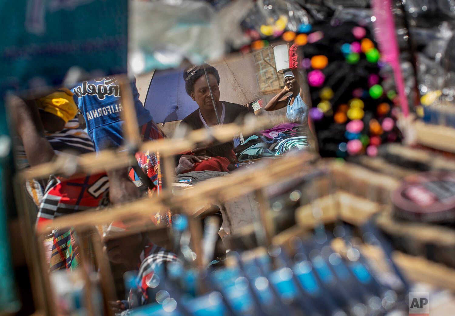 A street seller is seen reflected in mirrors for sale, at a market in the low income neighborhood of Mbare, known to have many supporters of former president Robert Mugabe's ZANU-PF party, in the capital Harare, Zimbabwe, Sept. 9, 2019. (AP Photo/Ben Curtis)