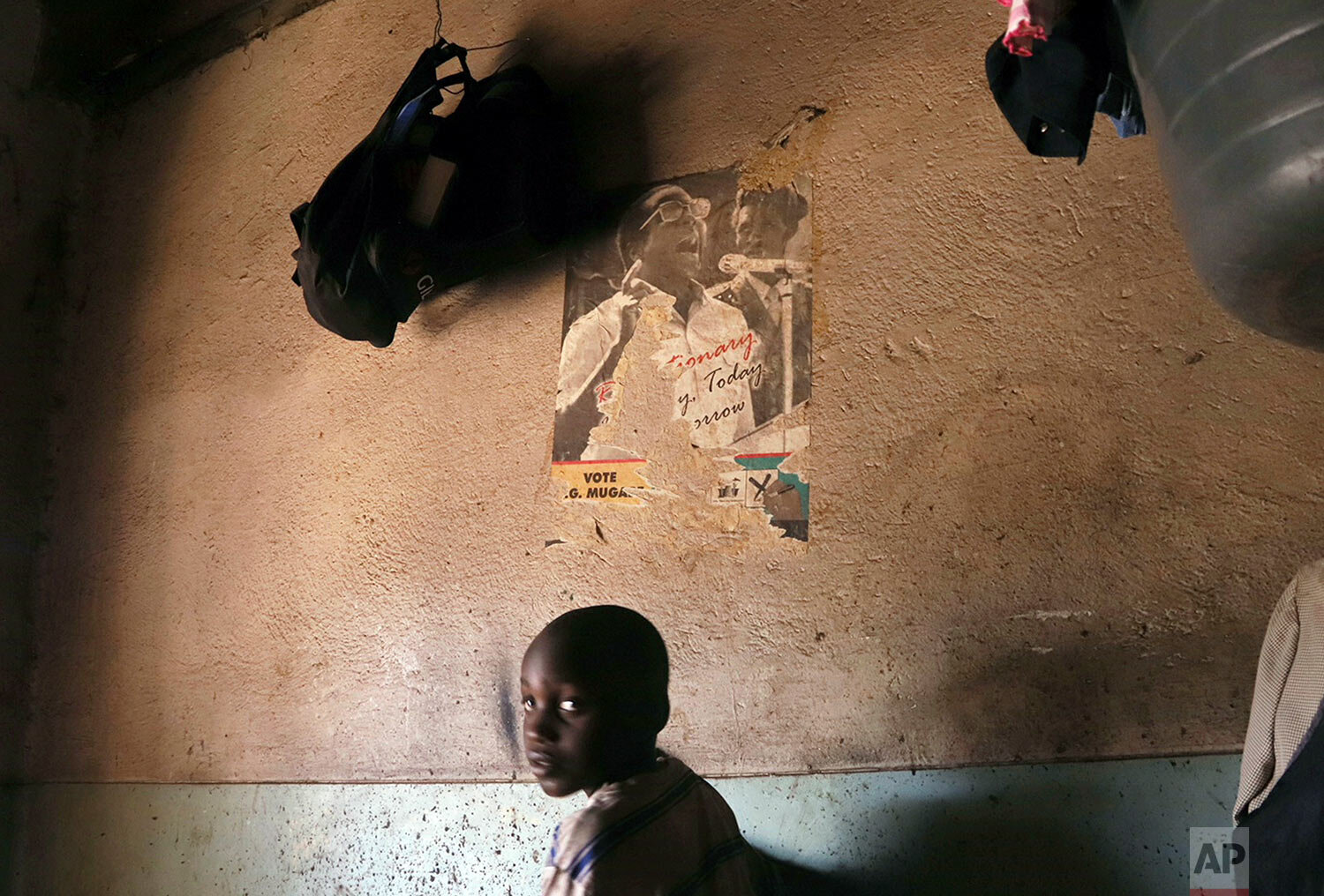 A young child walks past a poster of former Zimbabwean President Robert Mugabe in a building in Harare, Sept. 6, 2019. (AP Photo)