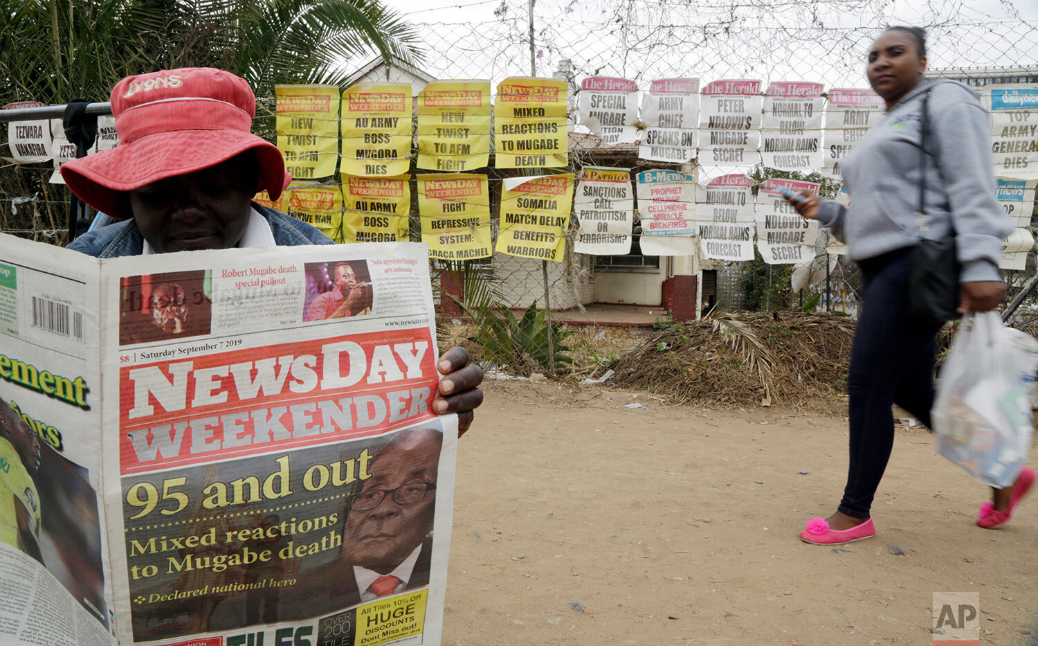 An ice cream vendor reads a newspaper on a street in Harare, Zimbabwe, Sept. 7, 2019. (AP Photo/Themba Hadebe)