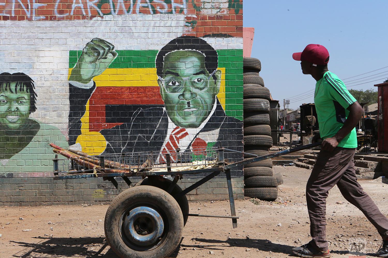 A man pushes an empty cart past a portrait of former Zimbabwean President Robert Mugabe in Harare, Sept. 6, 2019. (AP Photo/Tsvangirayi Mukwazhi)