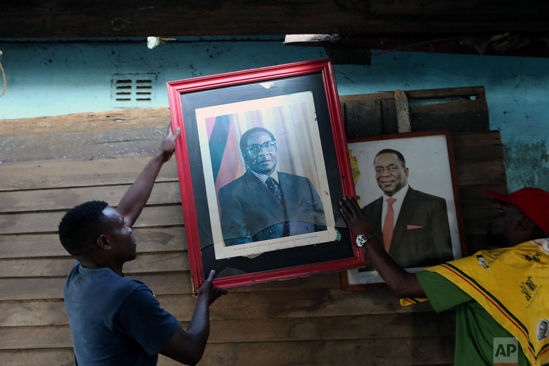 Supporters of former Zimbabwean President Robert Mugabe place his portrait next to that of Zimbabwean President Emmerson Mnangagwa in Harare, Sept, 10, 2019. Mnangagwa declared him a national hero. (AP Photo/Tsvangirayi Mukwazhi, File)