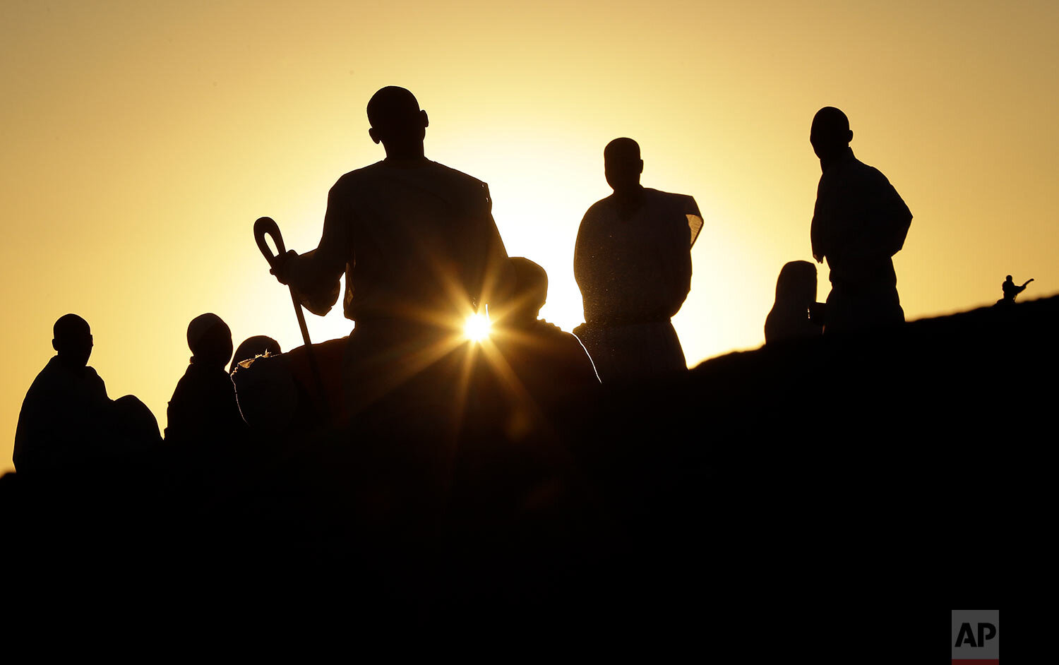 Zimbabweans sit and pray on top of a large rock on the outskirts of Harare, Zimbabwe, Sept. 8, 2019. (AP Photo/Themba Hadebe)