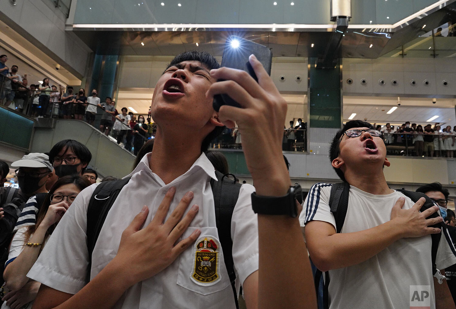 "Local residents sing a theme song written by protesters called""Glory be to thee"" at a shopping mall in Hong Kong Wednesday, Sept. 11, 2019. Hong Kong Chief Executive Carrie Lam reassured foreign investors Wednesday that the Asian financial hub can rebound from months of protests, despite no sign that the unrest will subside. (AP Photo/Vincent Yu)"