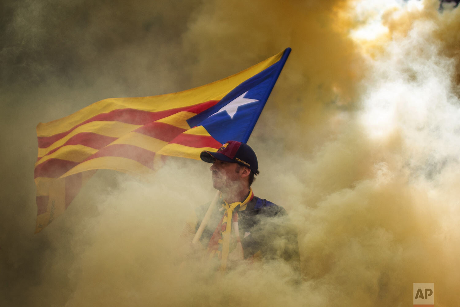 "A man holding an independence flag is seen through the smoke thrown by demonstrators during the Catalan National Day in Barcelona, Spain, Wednesday, Sept. 11, 2019. The traditional September 11, called ""Diada"", marks the fall of the Catalan capital to Spanish forces in 1714. (AP Photo/Emilio Morenatti)"
