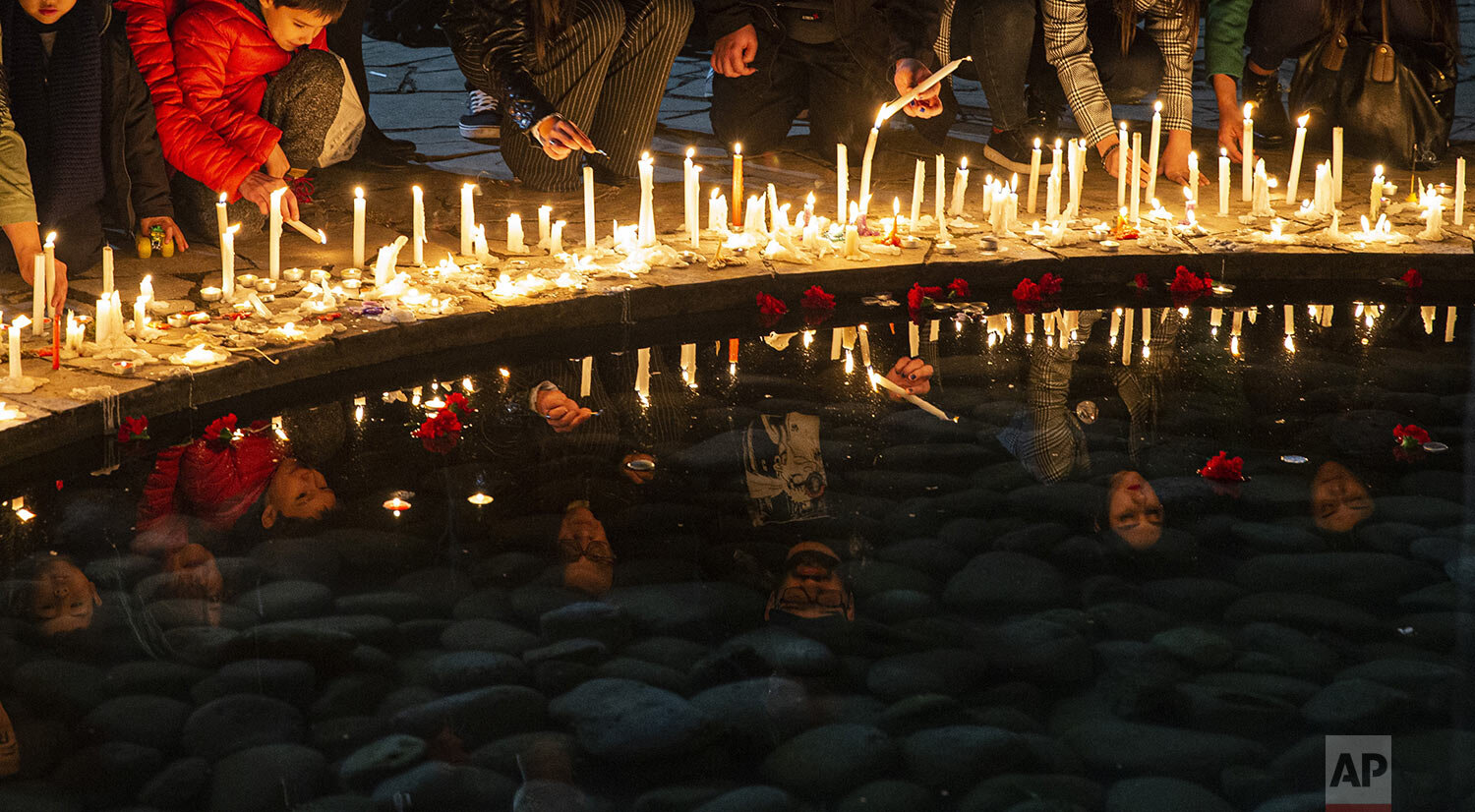 People light candles at the National Stadium during a vigil marking the anniversary of the 1973 military coup that ousted the late President Salvador Allende, in Santiago, Chile, Wednesday, Sept. 11, 2019. The stadium was used as a detention center in the early years of the dictatorship. (AP Photo/Esteban Felix)