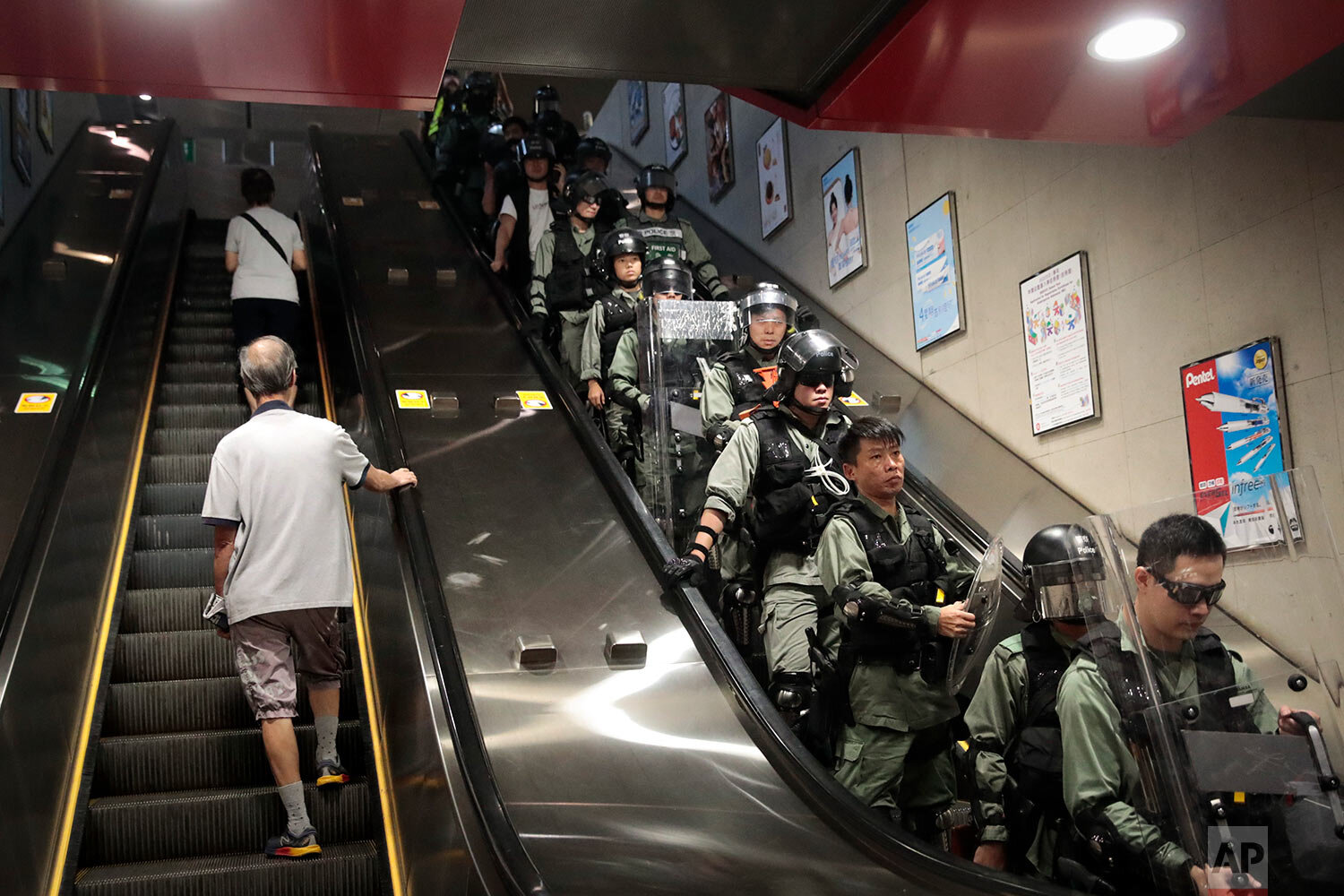 Two commuters ride an escalator at a train station past police officers in riot gear deployed to arrest protesters in Hong Kong, Sept. 2, 2019. (AP Photo/Jae C. Hong)