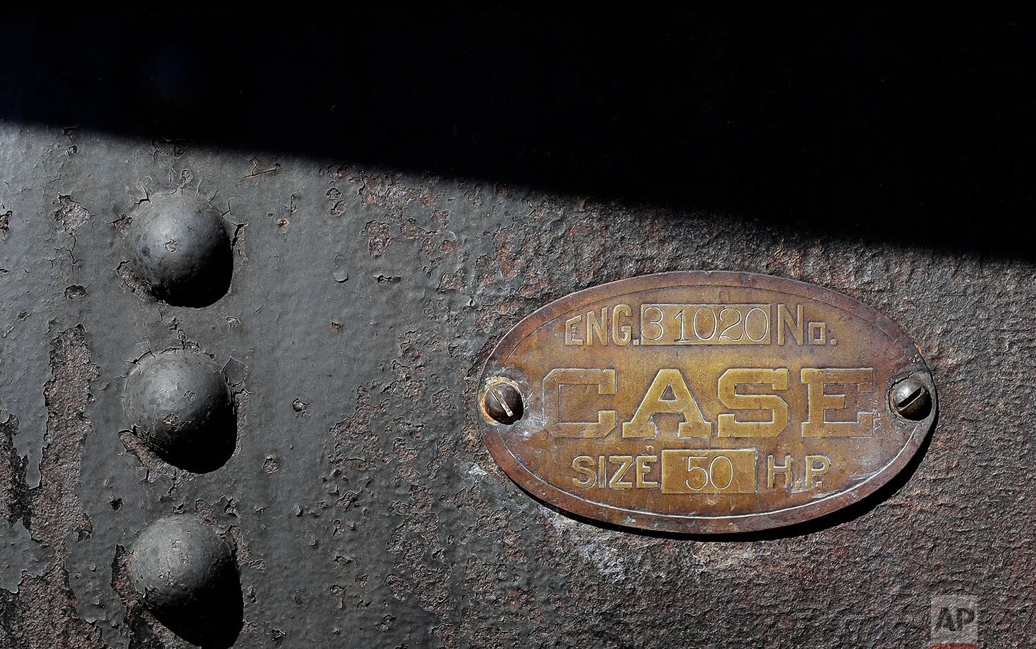 An identification plate on a 100-year-old Case steam traction engine indicates its power capacity at 50 horsepower as the machine is used to drive a stationary grain thresher near Colfax, Wash., Sept. 2, 2019. (AP Photo/Ted S. Warren)