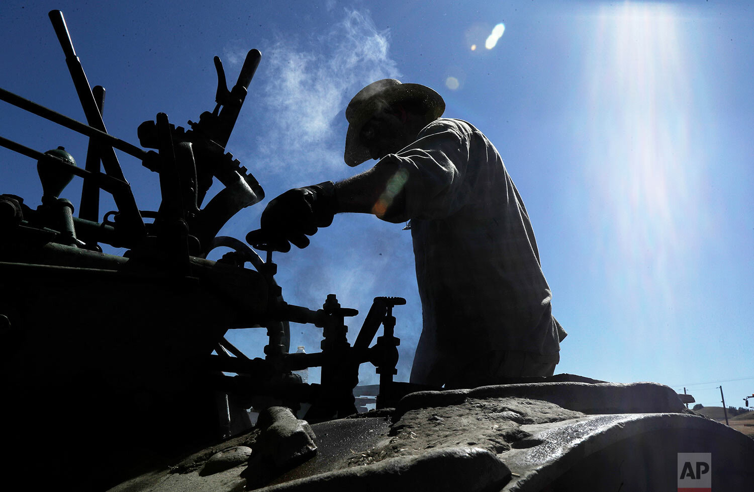 Charles Knaack operates a 100-year-old Case steam traction engine being used to drive a stationary grain thresher near Colfax, Wash., Sept. 2, 2019. (AP Photo/Ted S. Warren)