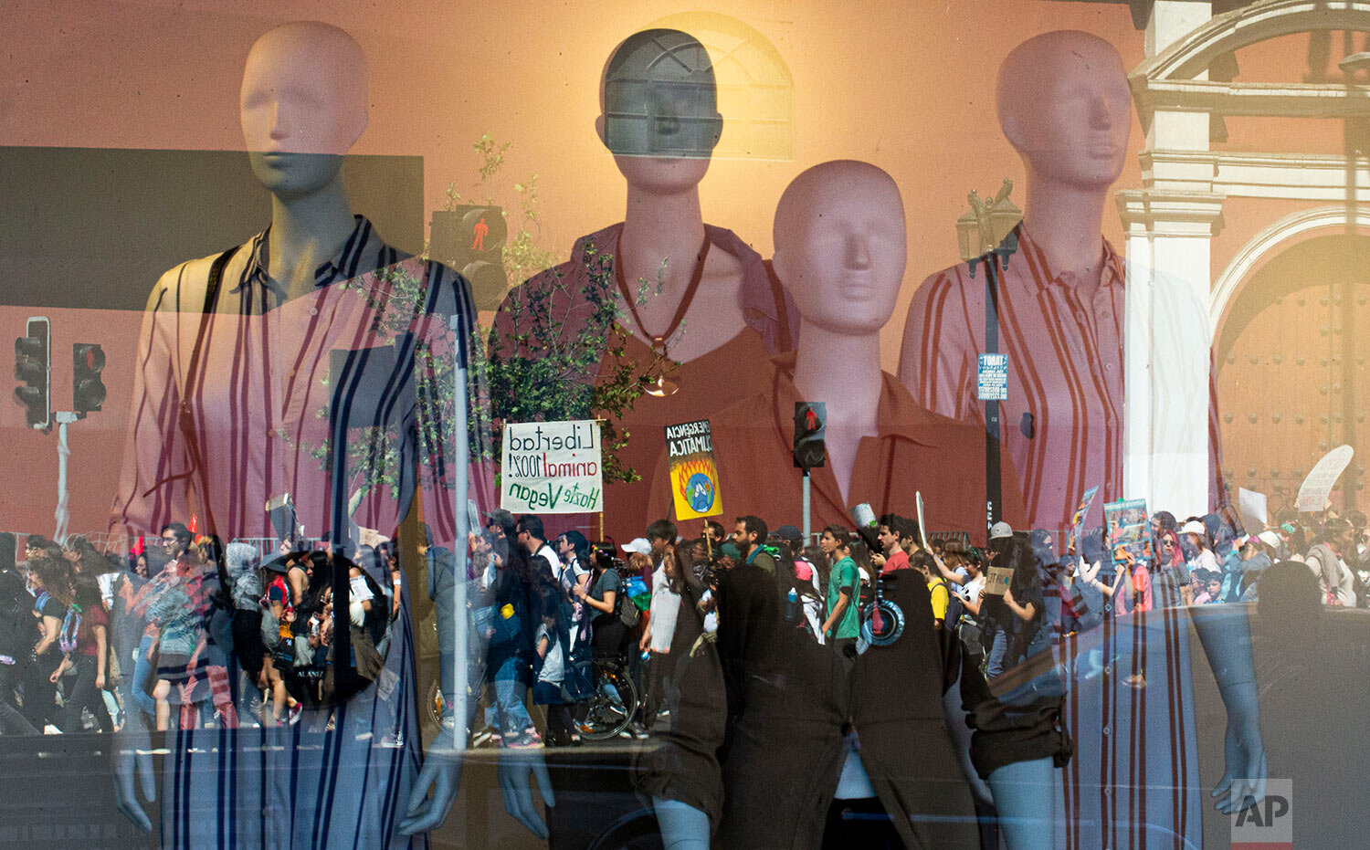 Demonstrators taking part in a global protest on climate change are reflected in a clothing store window, in Santiago, Chile, Friday, Sept. 20, 2019. Across the globe, hundreds of thousands took to the streets to demand that leaders tackle climate change in the run-up to a U.N. summit. (AP Photo/Esteban Felix)