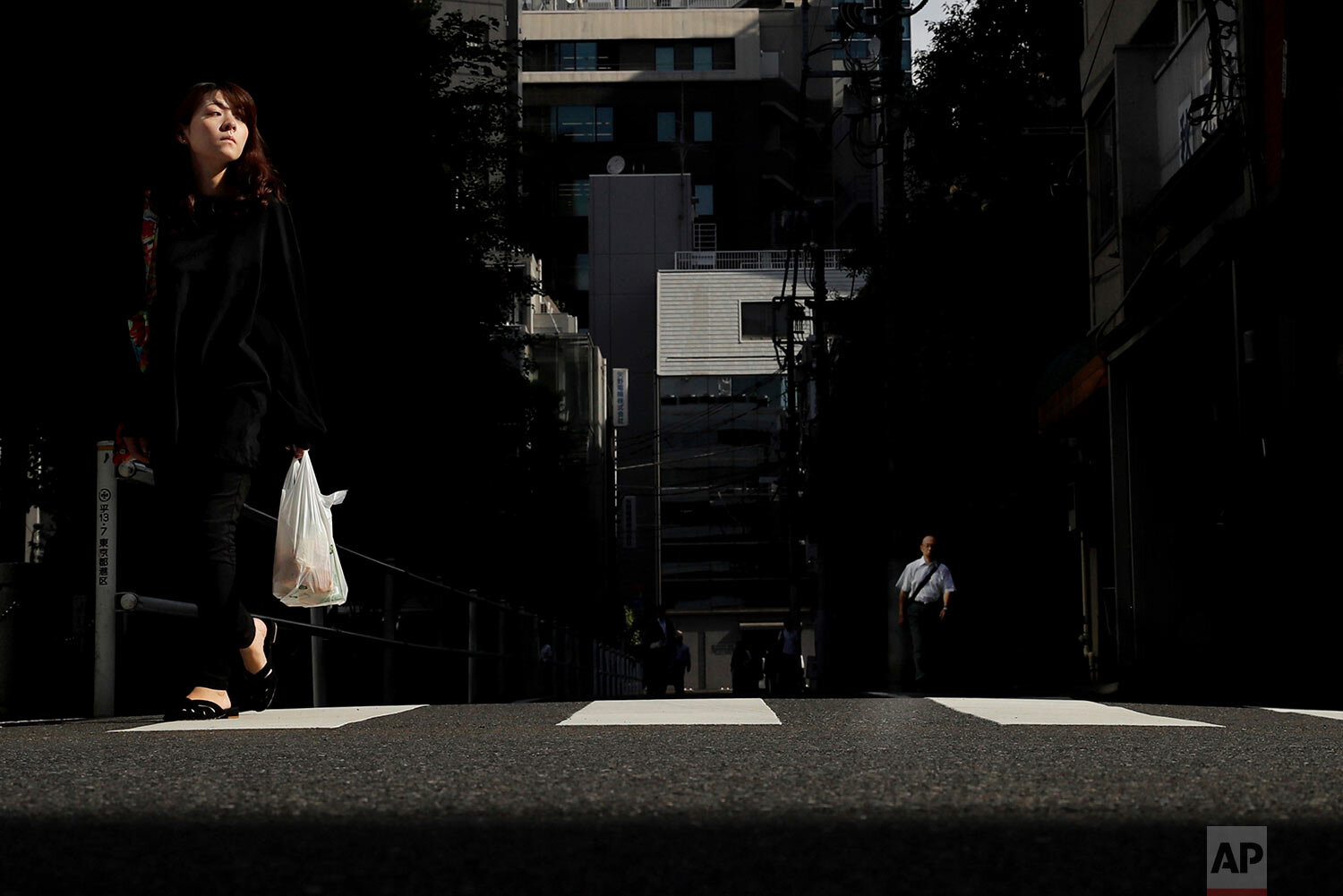 A woman crosses the street in the Shinbashi district of Tokyo, Japan, Friday, Sept. 20, 2019. (AP Photo/Christophe Ena)